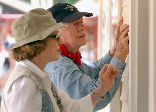 Jimmy Carter and his wife, Rosalynn, attach siding to the front of a Habitat for Humanity home being built on June 10, 2003, in LaGrange, Ga. More than 90 homes are being built in LaGrange; Valdosta, Georgia; and Anniston, Alabama by volunteers as part of Habitat for Humanity International's Jimmy Carter Work Project 2003.
