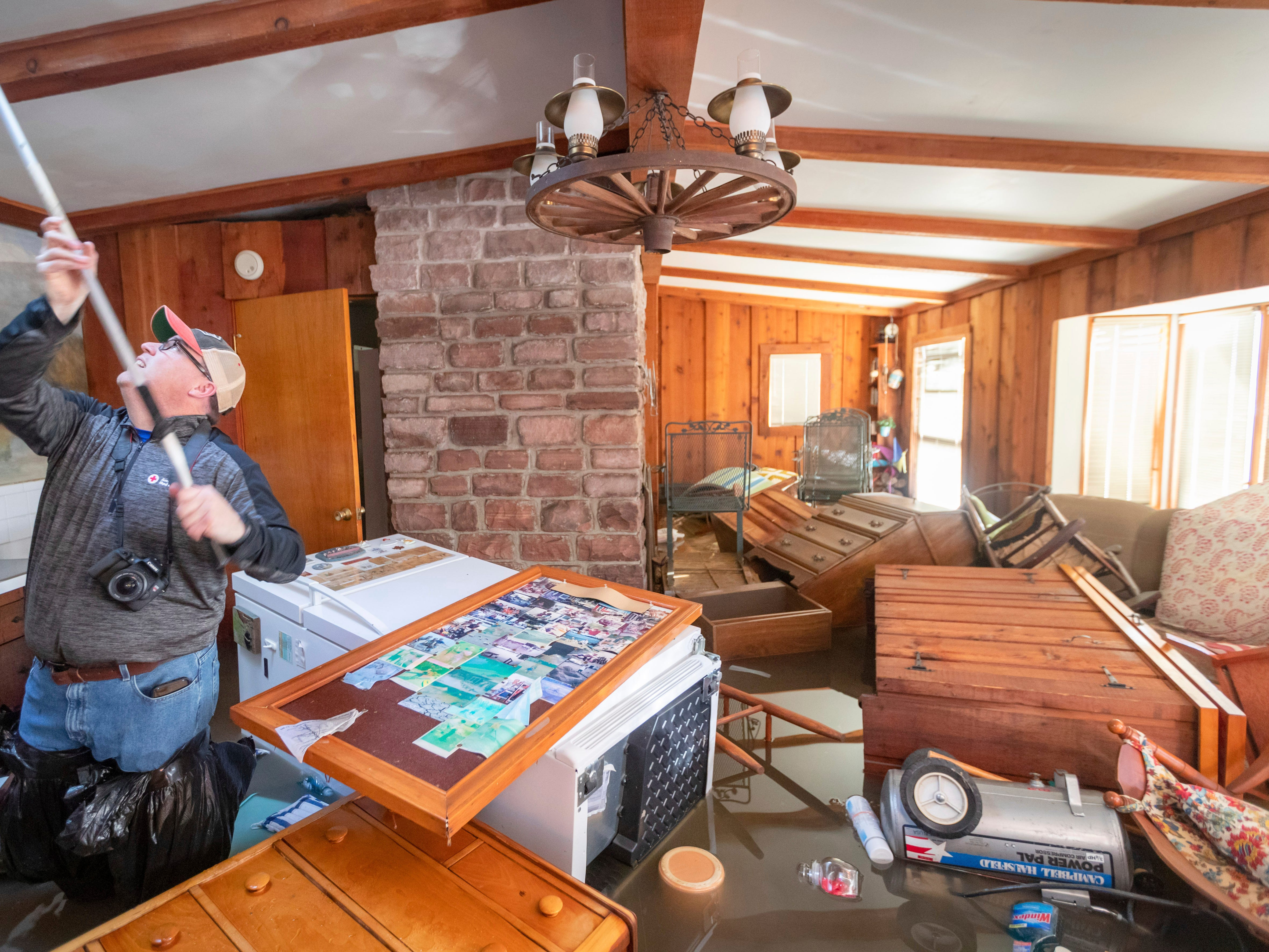 Steve O'Donnell works to open a skylight while standing in floodwaters inside a home Friday, March 22, 2019, in Bellevue, Neb.