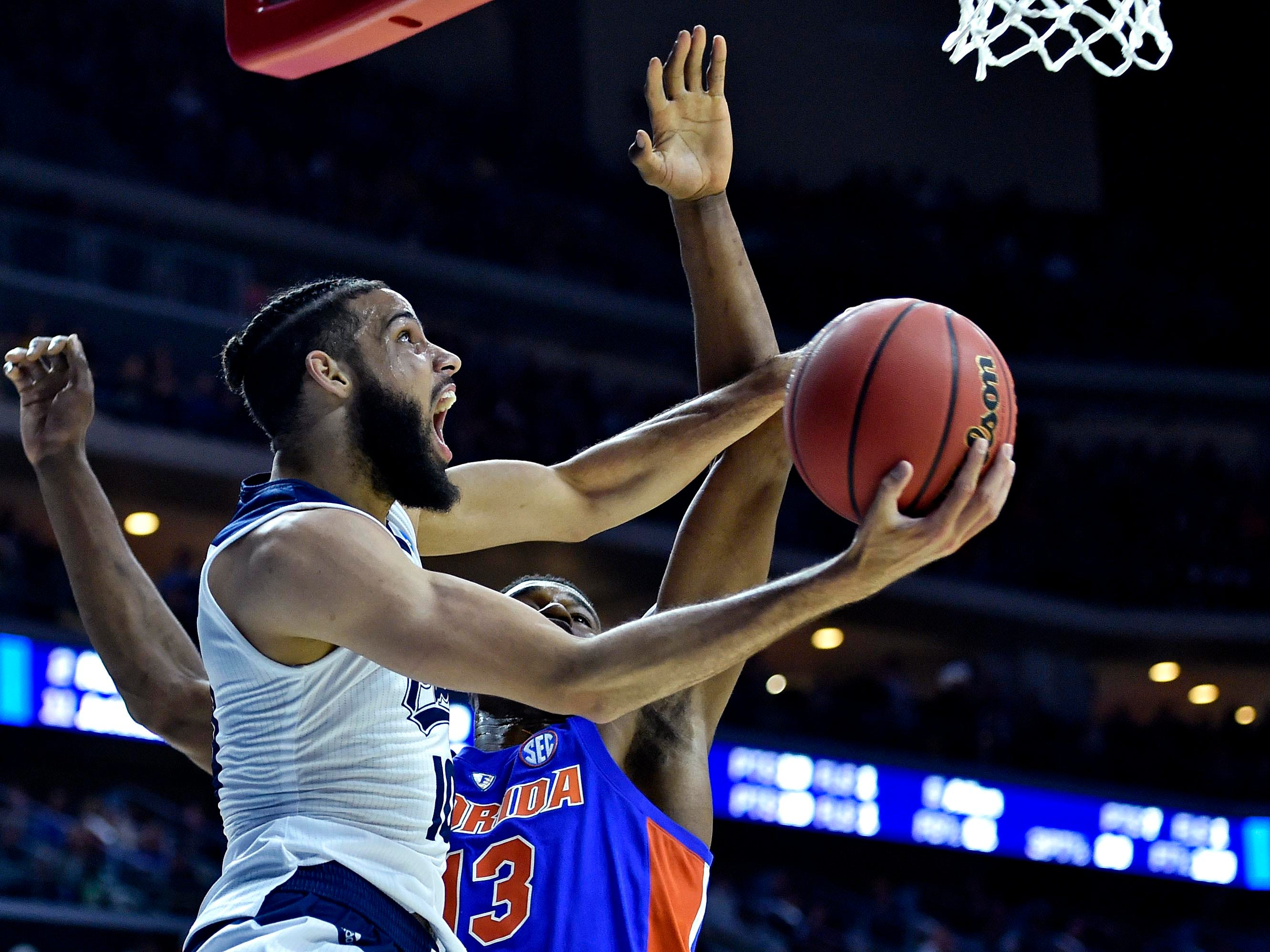 First round: Nevada forward Caleb Martin drives to the basket against Florida center Kevarrius Hayes. Martin struggled in the loss, shooting just 5-22 from the field.