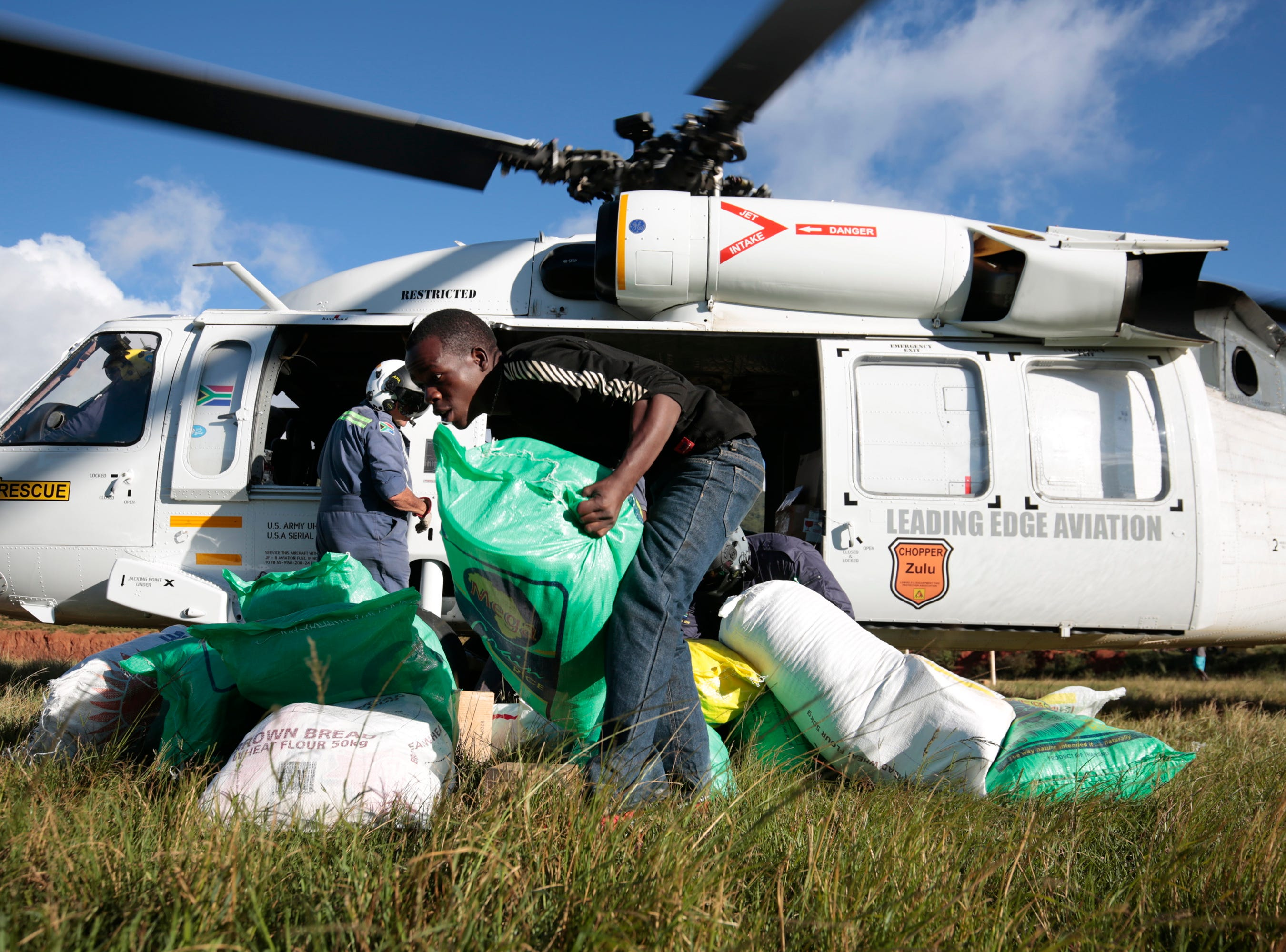 A helicopter brings relief aid in Ngangu, Chimanimani, some 550km east of Harare, Zimbabwe on March 22, 2019, following the passage of Cyclone Idai. More than 200 people are believed to have died with hundreds injured, several missing and thousands displaced after Cyclone Idai struck Zimbabwe. President Emmerson Mnangagwa has declared Cyclone Idai a national disaster. Neighboring countries such Zambia, Namibia, and South Africa have offered material help to the affected people and areas.