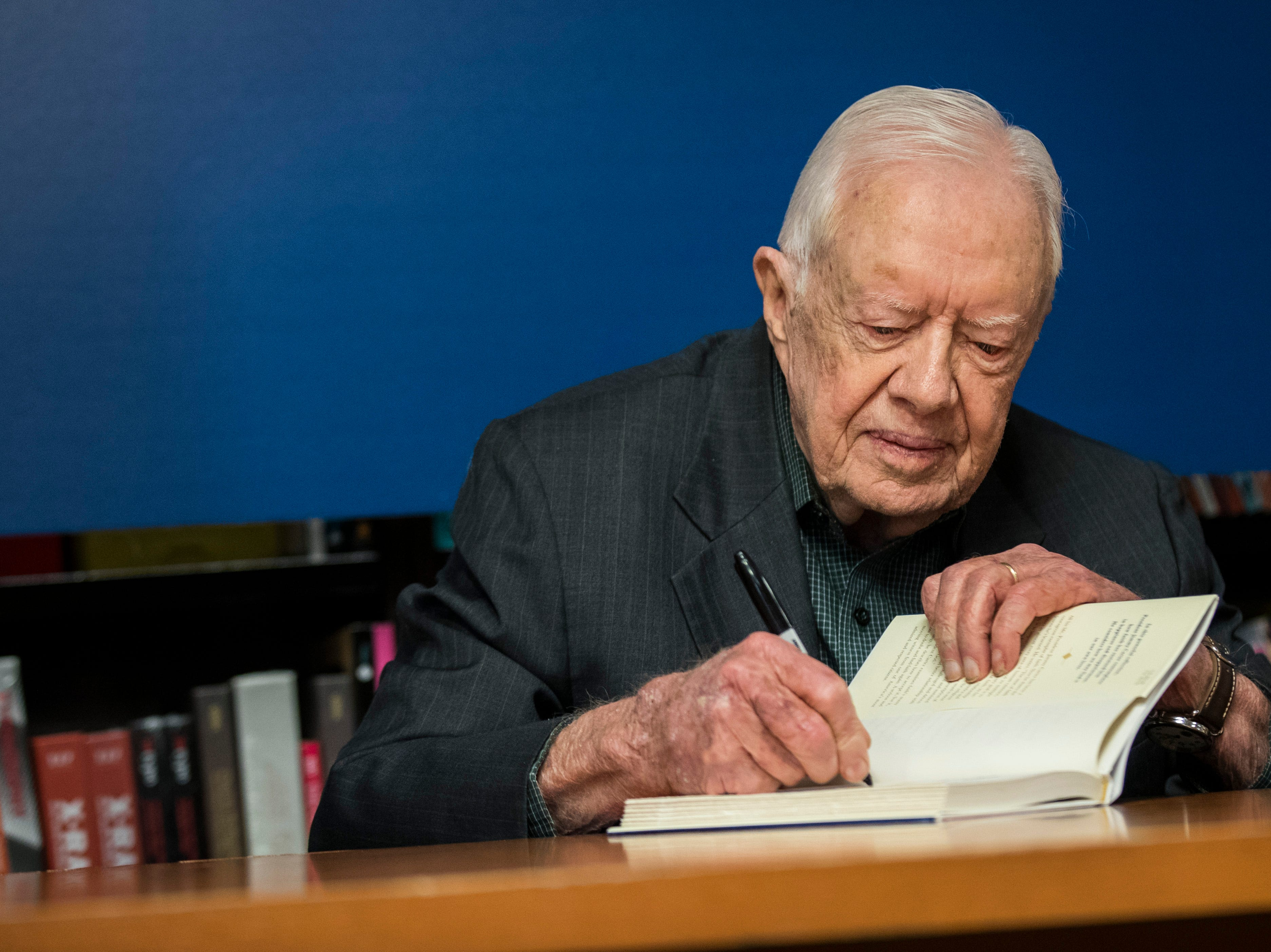 "Jimmy Carter signs a copy of his book ""Faith: A Journey for All"" at a book signing event at Barnes & Noble in Midtown Manhattan on March 26, 2018, in New York."