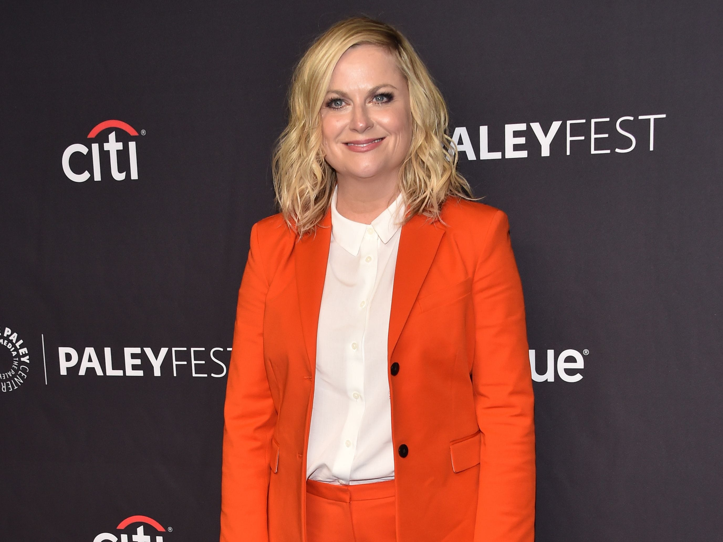 "Amy Poehler arrived in a pantsuit in a pantsuit and sneakers her ""Parks and Rec"" character, Leslie Knope, would have liked."