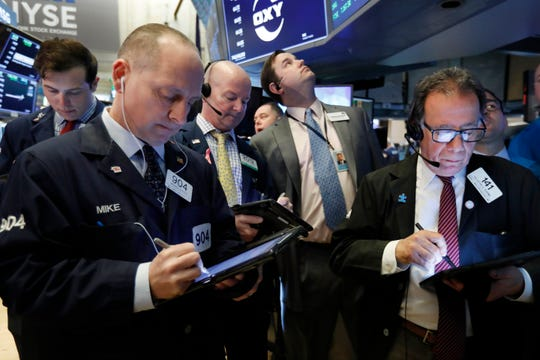 Traders gather on the floor of the New York Stock Exchange on March 13, 2019.