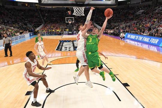 Ethan Happ (22) blocks a shot by Oregon's Payton Pritchard.