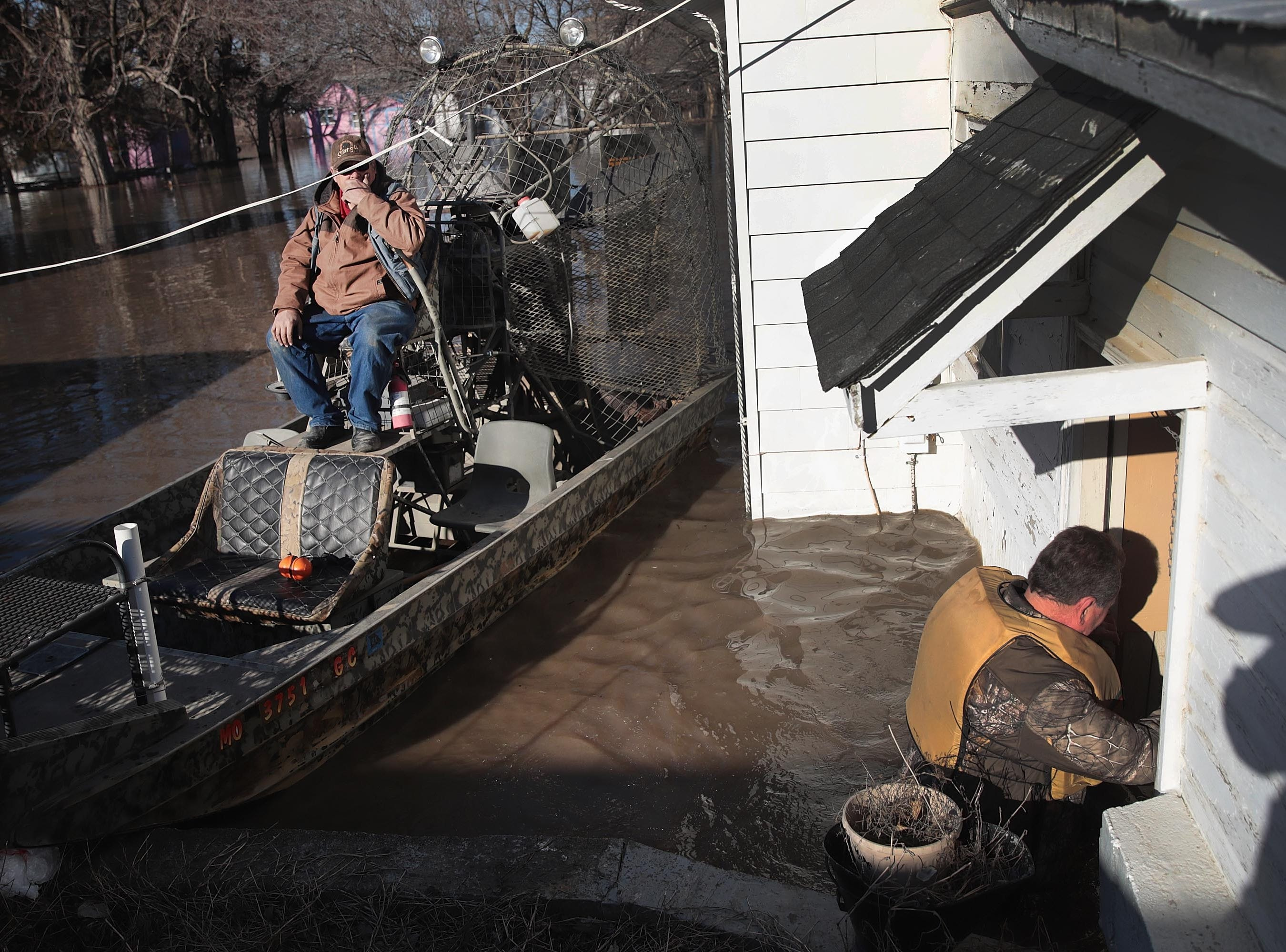 Rick Johnson, left, helps Larry Whetsel recovers possessions from his flooded home on March 21, 2019 in Craig, Missouri.