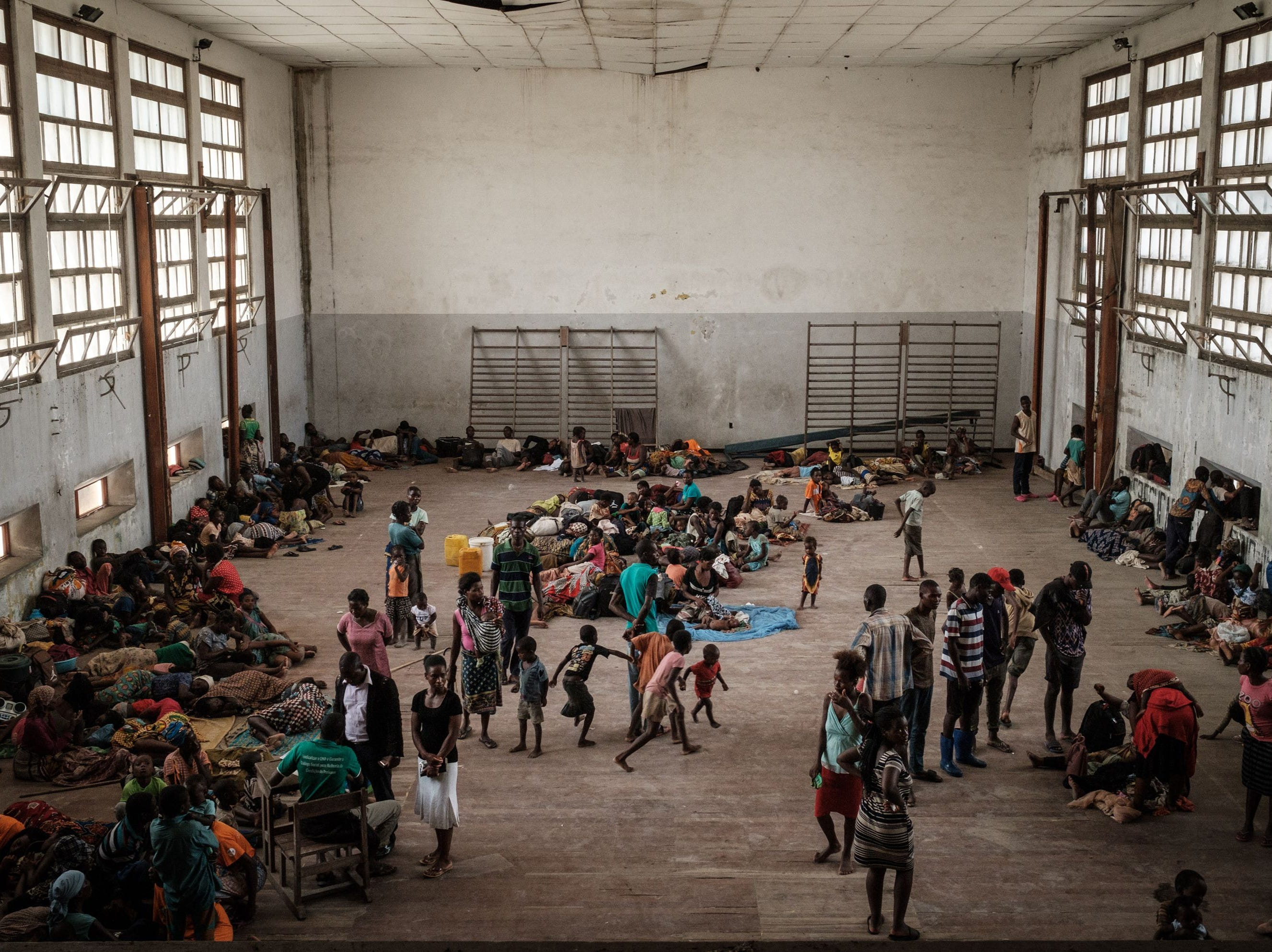 People from the isolated district of Buzi take shelter in the Samora M. Machel secondary school used as an evacuation center in Beira, Mozambique, on March 21, 2019, following the devastation caused by Cyclone Idai.  Aid workers raced against time to help survivors and meet spiraling humanitarian needs in three southern African countries battered by the region's worst storm in years. Six days after tropical cyclone Idai cut a swathe through Mozambique, Zimbabwe and Malawi, the confirmed death toll stood at more than 300 and hundreds of thousands of lives were at risk, officials said.