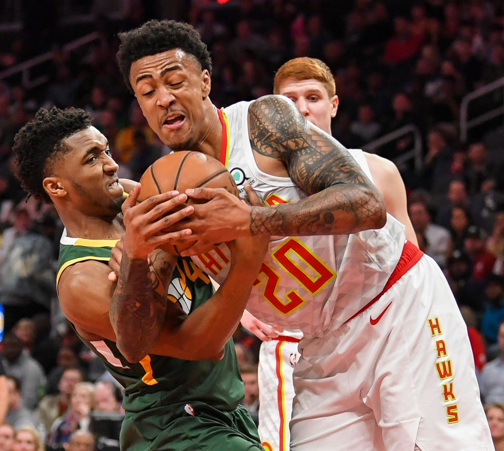 March 21: Atlanta Hawks forward John Collins (20) and Utah Jazz guard Donovan Mitchell fight for the ball during the second half at State Farm Arena. The Hawks won the game, 117-114.