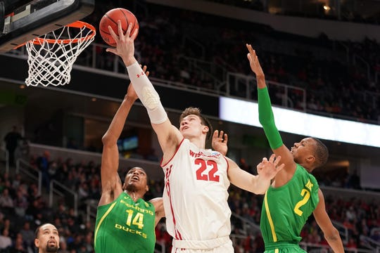 Wisconsin forward Ethan Happ puts up a shot against Oregon's Kenny Wooten (14) and Louis King.