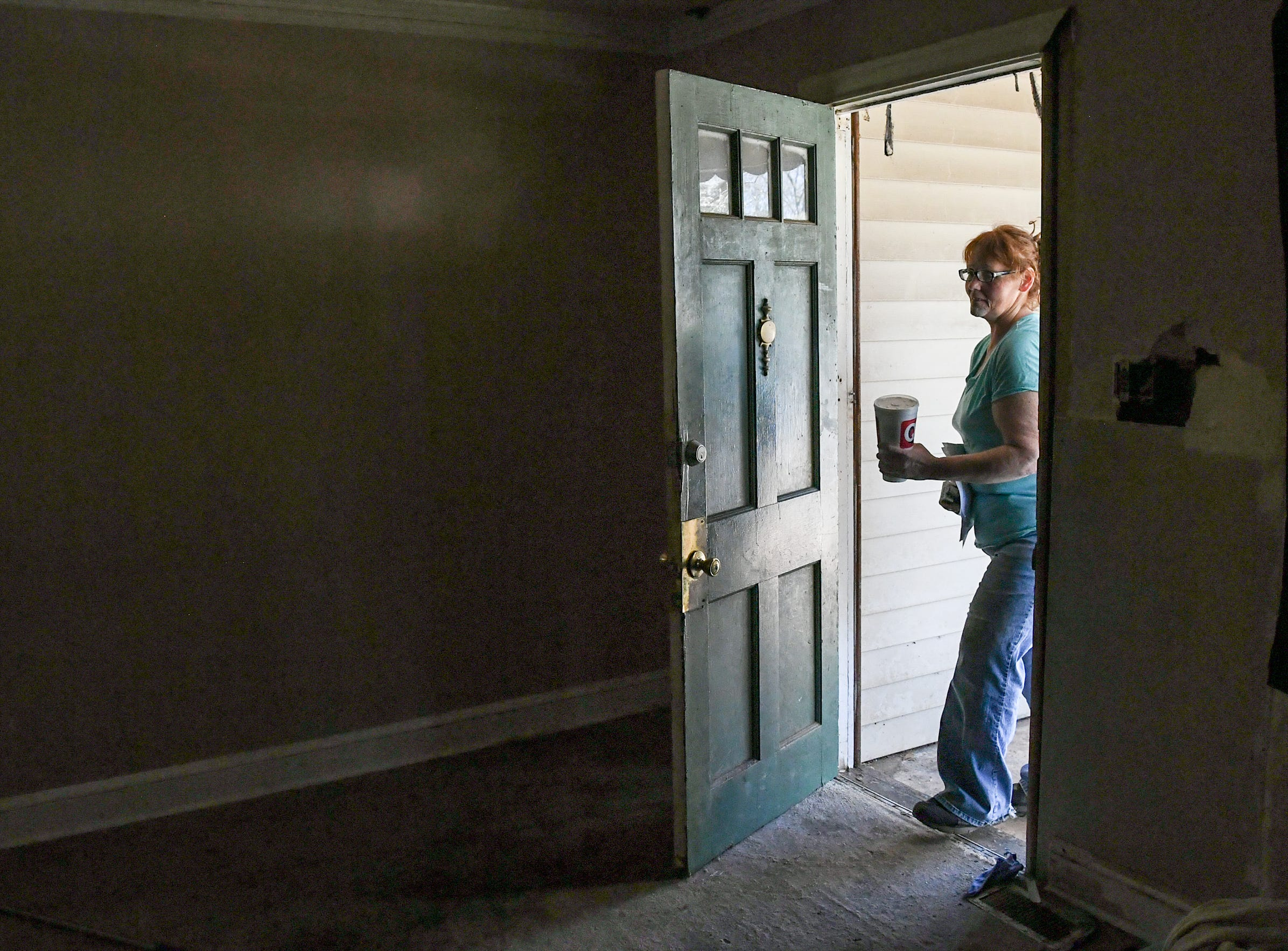 Kristy Drees of Anderson enters the rental home in Homeland Park with little power on during the day in March. Drees says her unemployment, looming water bill, and courtroom battles with her landlord is stressful.