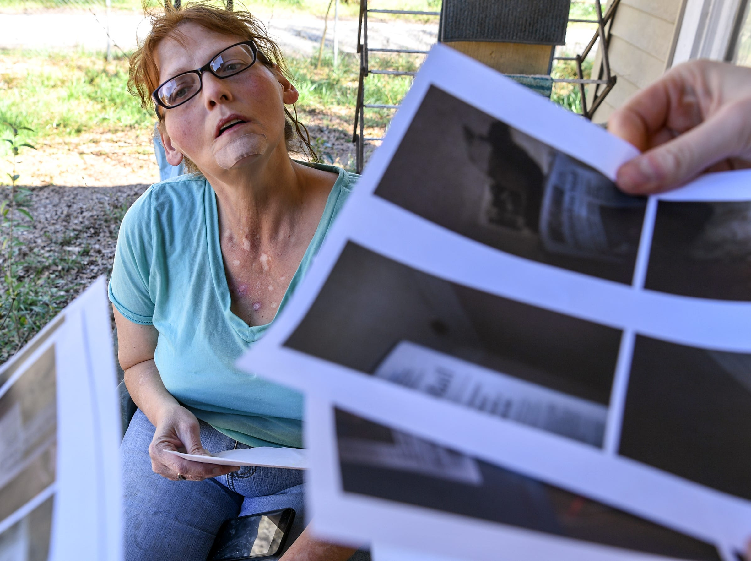 Kristy Drees of Anderson looks at photos showing issues of water and electrical she thinks the landlord needs to repair.