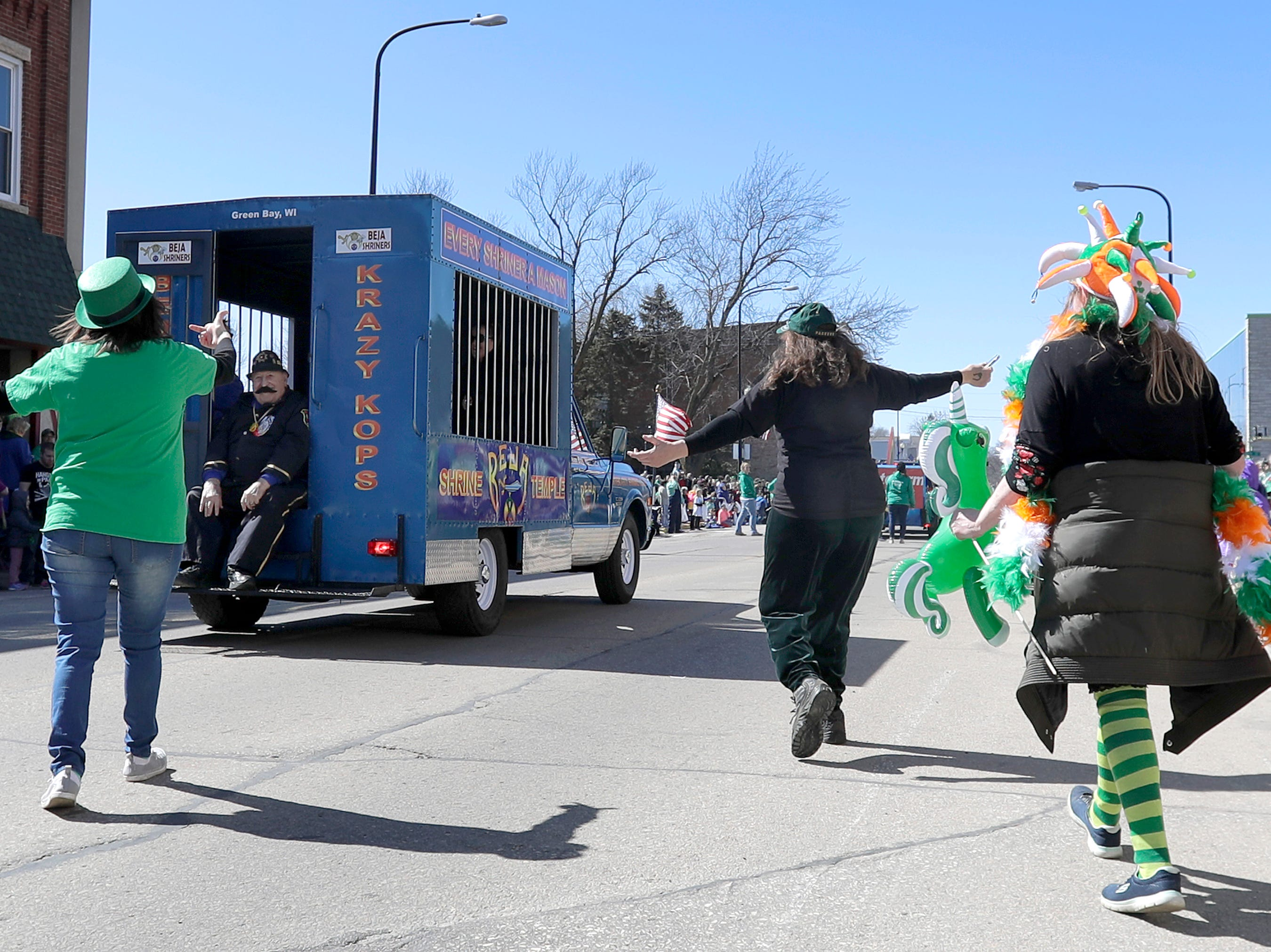 """Parade goers try to get """"arrested"""" by the Krazy Kops during the New Dublin St. Patrick's Day Grand Parade on Saturday, March 23, 2019, in New London, Wis.Wm. Glasheen/USA TODAY NETWORK-Wisconsin."""