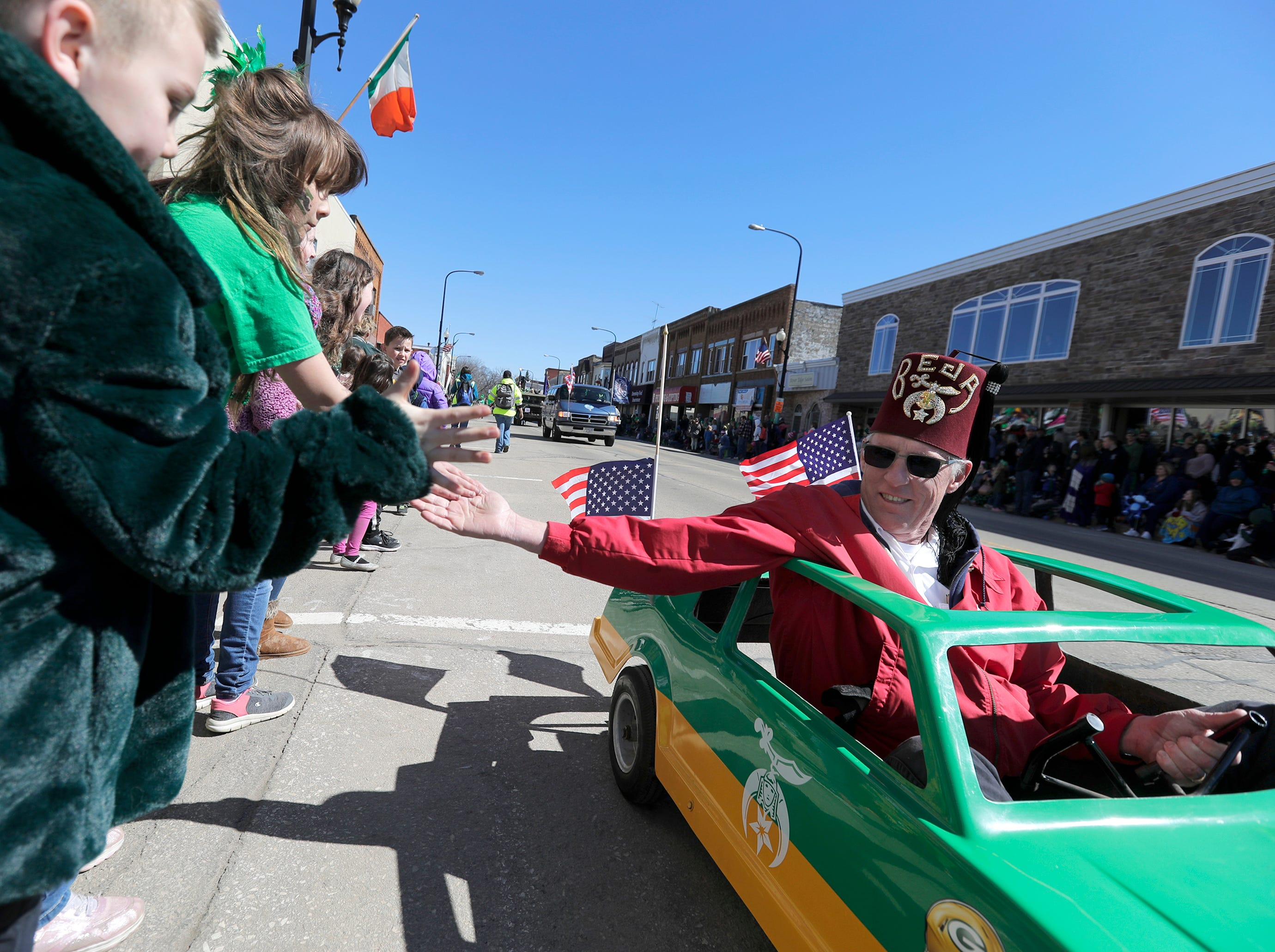 Shriner Dennis Clark shakes hands during the New Dublin St. Patrick's Day Grand Parade on Saturday, March 23, 2019, in New London, Wis.Wm. Glasheen/USA TODAY NETWORK-Wisconsin.