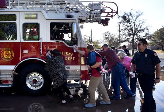 Firefighters and Abilenians push the Abilene Fire Department's new Ladder 5 into its bay at Station No. 5 on Saturday morning.