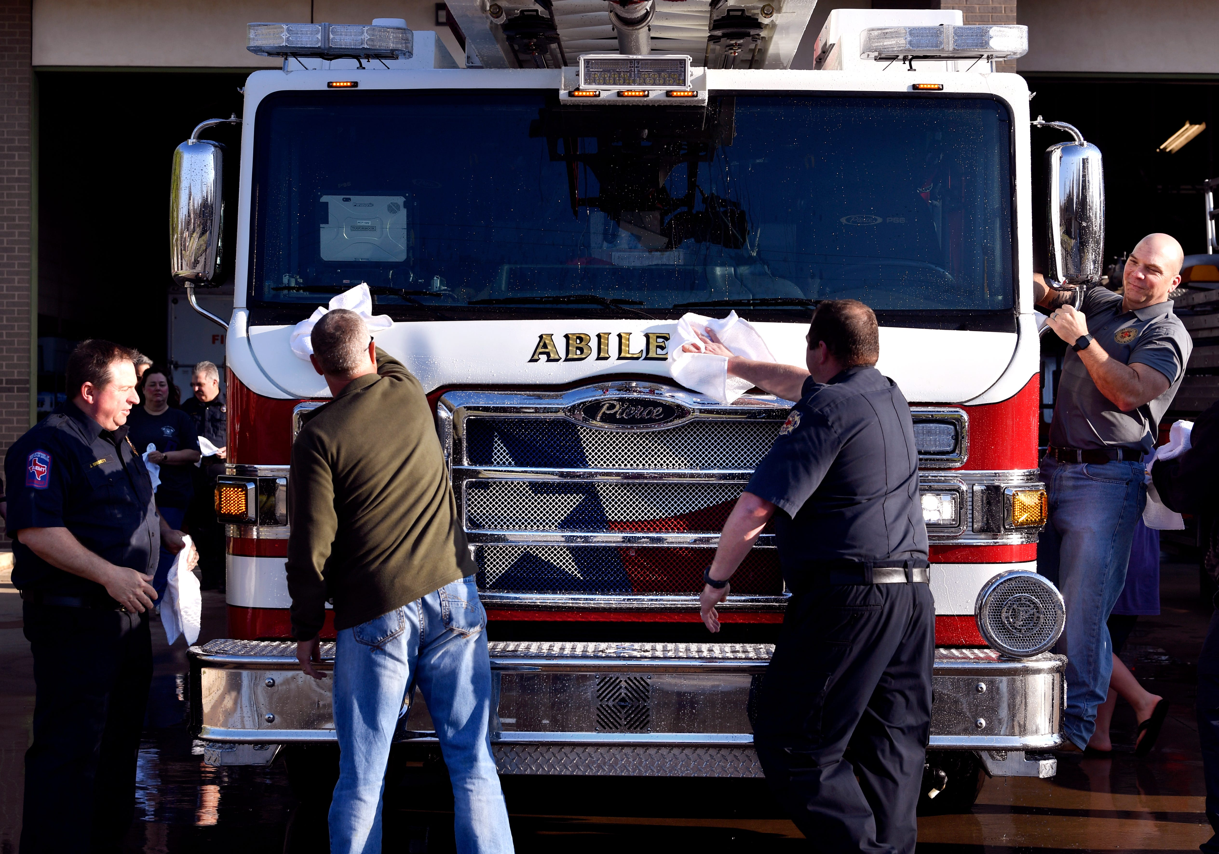 Abilene firefighters and guests wipe Ladder 5 at Station No. 5 during a welcoming ceremony for the new equipment Saturday morning. The truck, a Pierce Ascendant, features a remote-controlled nozzle and LED lighting along the 100-foot ladder.
