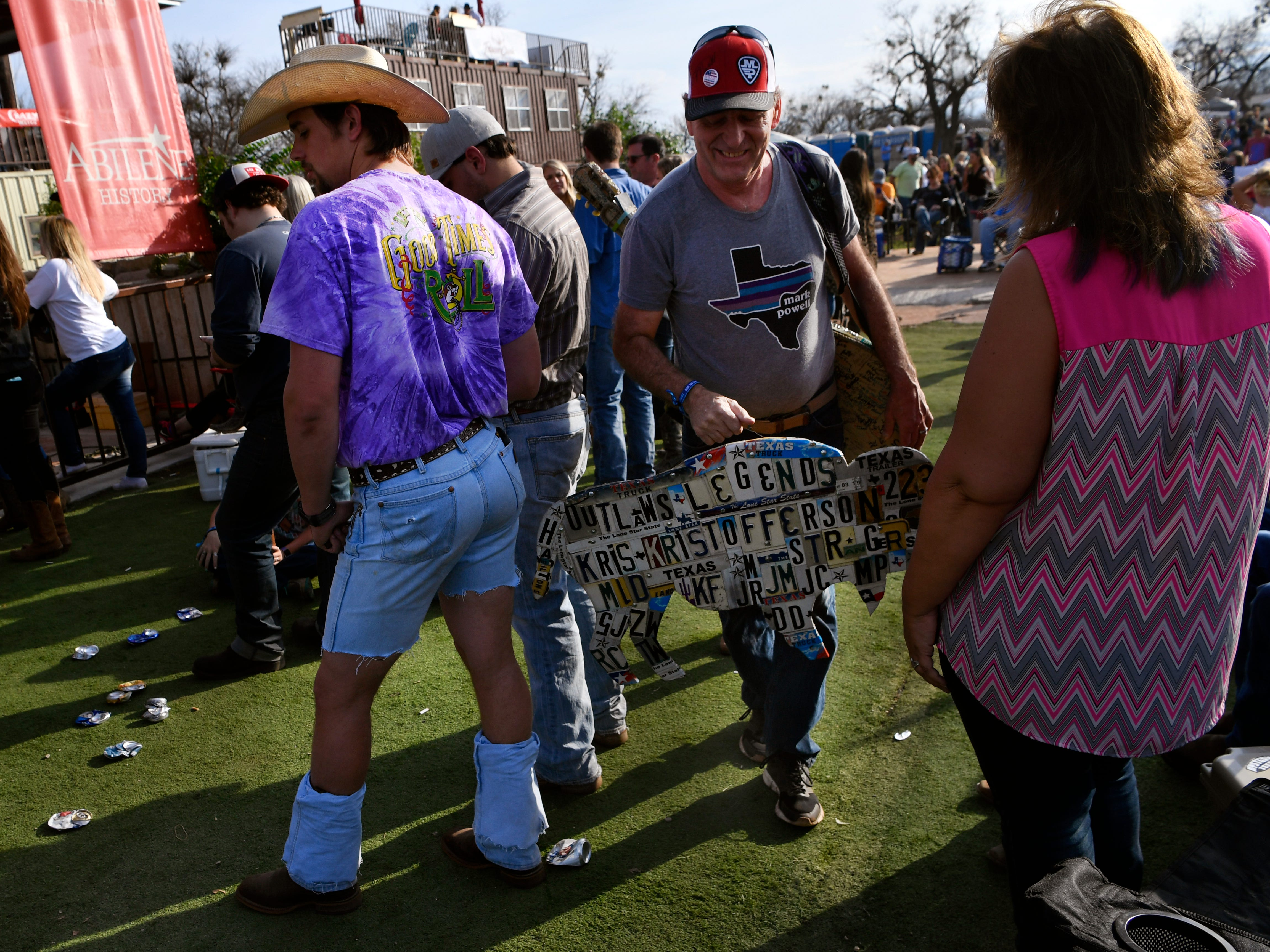 Dennis Gross carries his custom artwork he made for the festival made through the crowd at the Outlaws & Legends music festival Friday March 22, 2019. Gross cut a buffalo shape in wood and then used old license plates to spell the names of this year's performers.