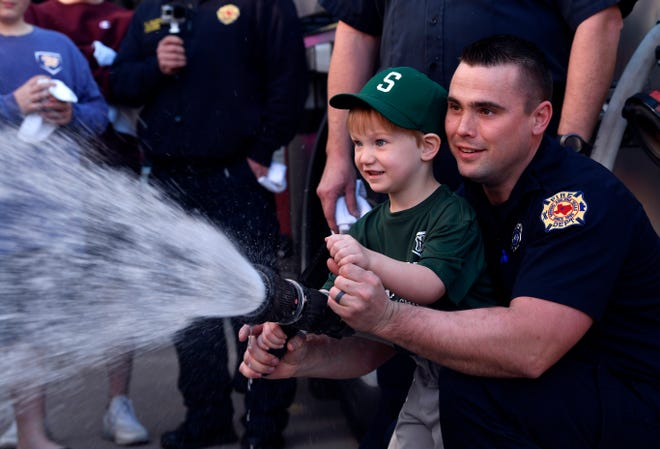 Michael Easley with the Abilene Fire Department helps his son Hank, 3, hose the Ladder 5 firetruck during Saturday's welcoming ceremony for the new equipment at Station No. 5. The truck, a Pierce Ascendant, features a remote-controlled nozzle and LED lighting along the 100-foot ladder. Station No. 5 serves the area around Abilene Christian University and is located on E.N. 16th Street.