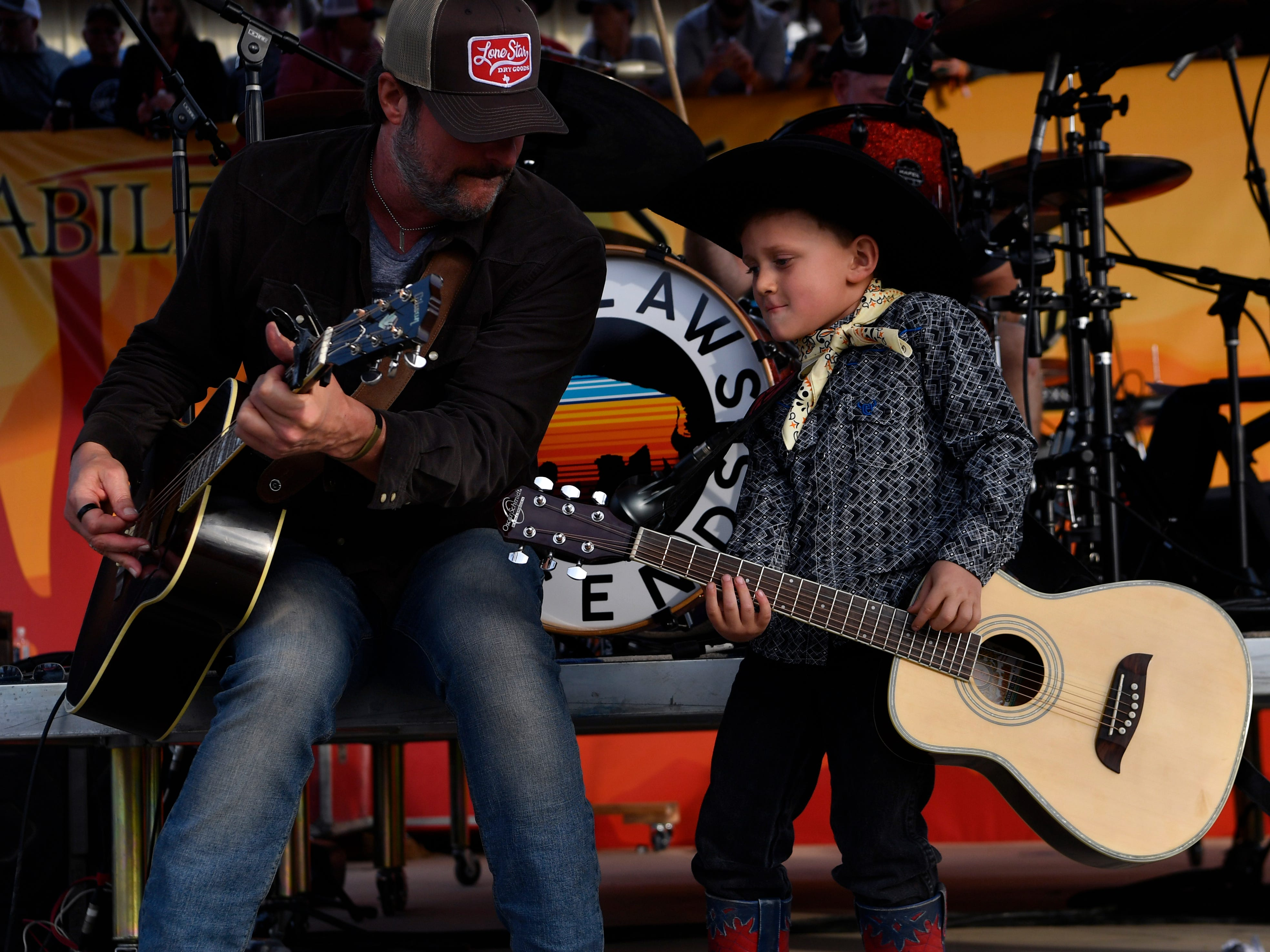 Bubba Crabtree, 6, strums onstage with Deryl Dodd during Friday's Outlaws & Legends music festival March 22, 2019.