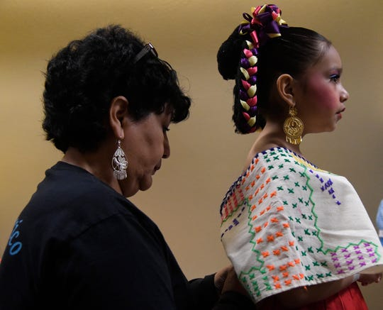 Mary Carmen Pena adjusts seven-year-old Isabella Esparza's Michoc‡n costume before her dance at the Selena Auditorium, Saturday, March 23, 2019. Esparza has been dancing since she was two and a half.