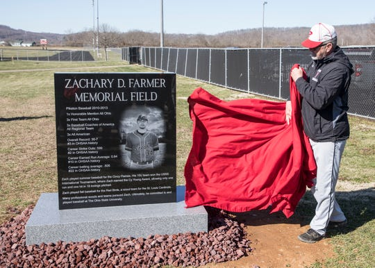 Zach Farmer's dad Larry Farmer removes the covering to show the new monument at Piketon's baseball field that honors his son Zach, who passed away in 2015 from Leukemia.