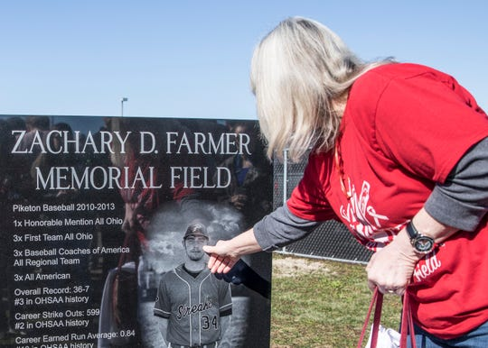 Zach Farmer's mother Tammy takes a moment and touches her son's photo after the dedication Saturday morning at the Piketon baseball field.