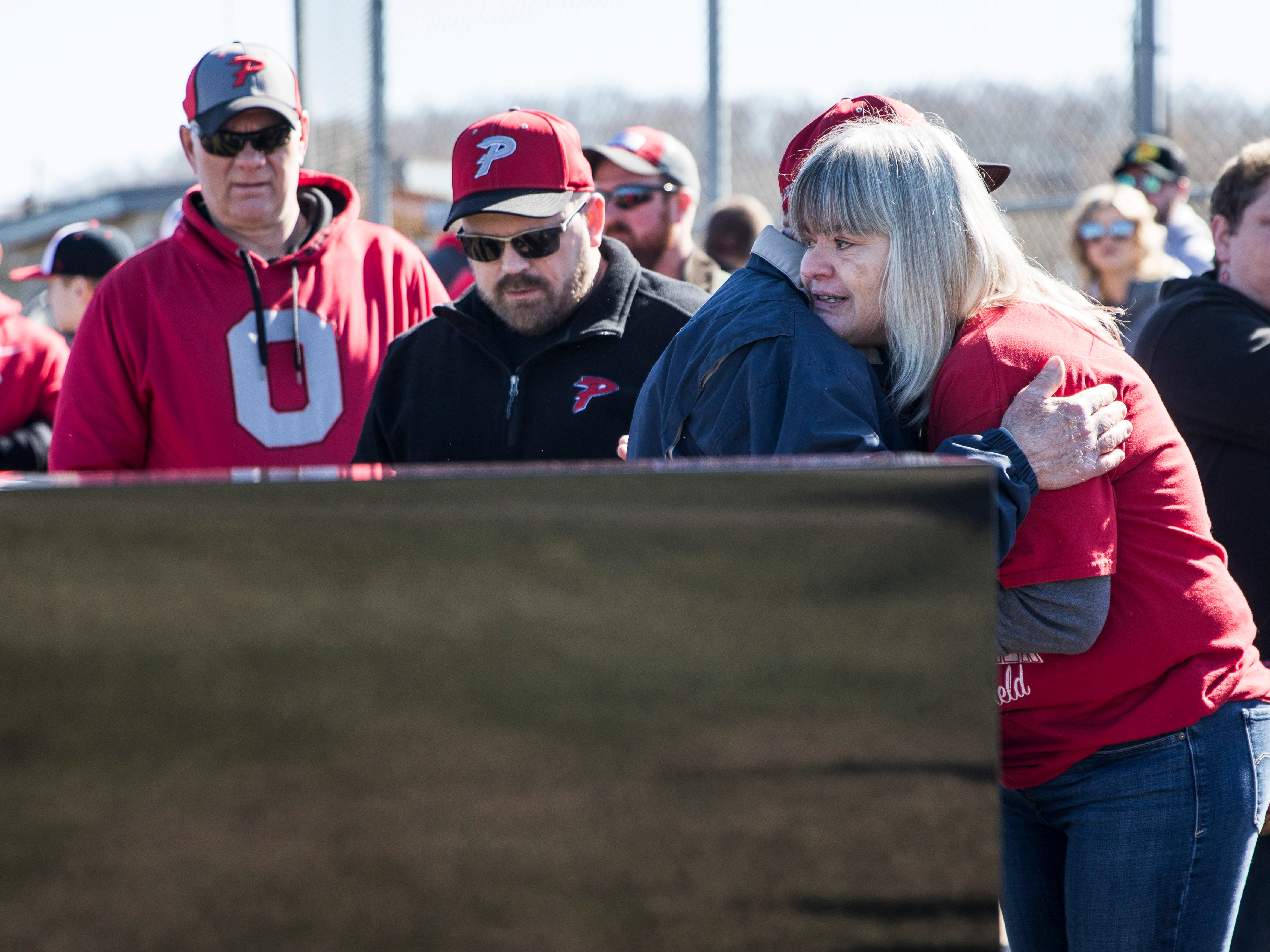 Tammy Farmer receives several condolence hugs after the dedication of her son's monument at the Piketon baseball field Saturday morning.