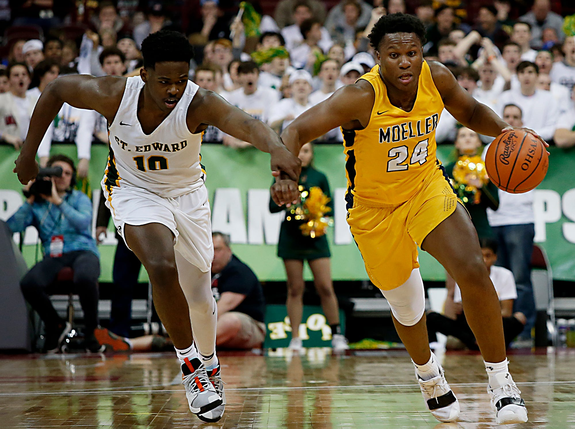 Moeller forward Alex Williams is pursued by St. Edward guard/forward Devontae Blanton during their Division I semifinal at the Schottenstein Center in Columbus Friday, March 22, 2019.