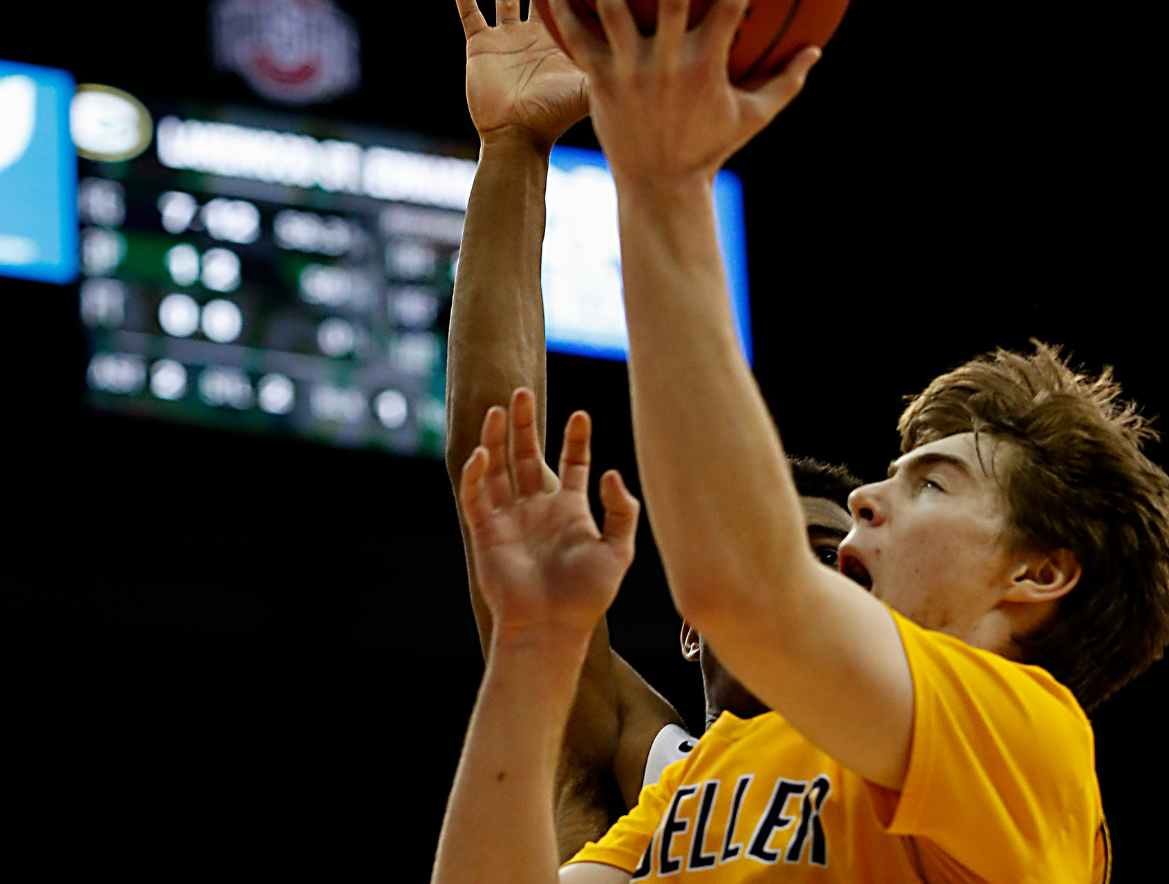 Moeller forward Alec Pfriem gets the basket despite the pressure from St. Edward guard Montorie Foster during their Division I semifinal at the Schottenstein Center in Columbus Friday, March 22, 2019.