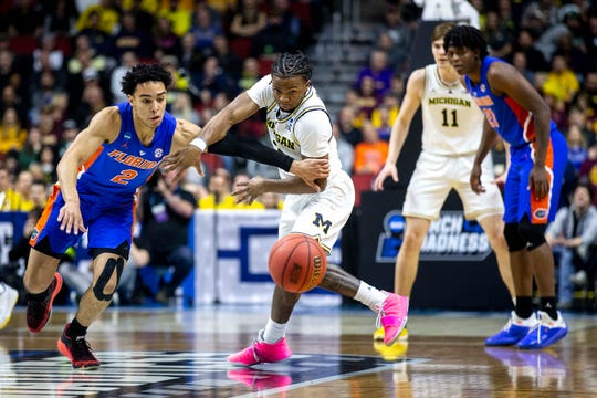 Florida's Andrew Nembhard and Michigan's Zavier Simpson fight for the loose ball during the NCAA Tournament second-round match-up between Michigan and Florida on Saturday, March 23, 2019, in Wells Fargo Arena in Des Moines, Iowa.