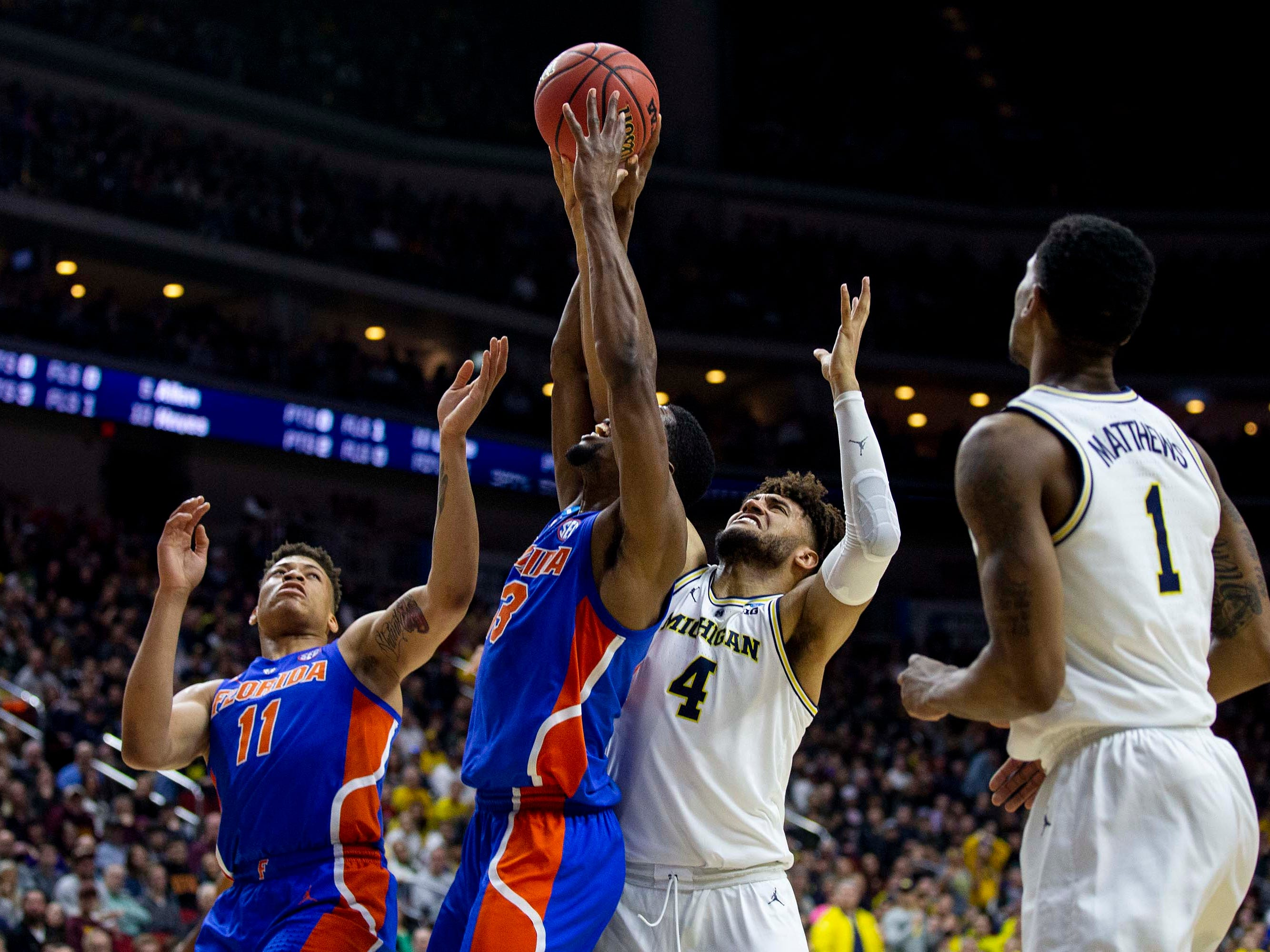 Florida's Keyontae Johnson, Kevarrius Hayes and Michigan's Isaiah Livers reach for a rebound during the NCAA Tournament second-round match-up between Michigan and Florida on Saturday, March 23, 2019, in Wells Fargo Arena in Des Moines, Iowa.