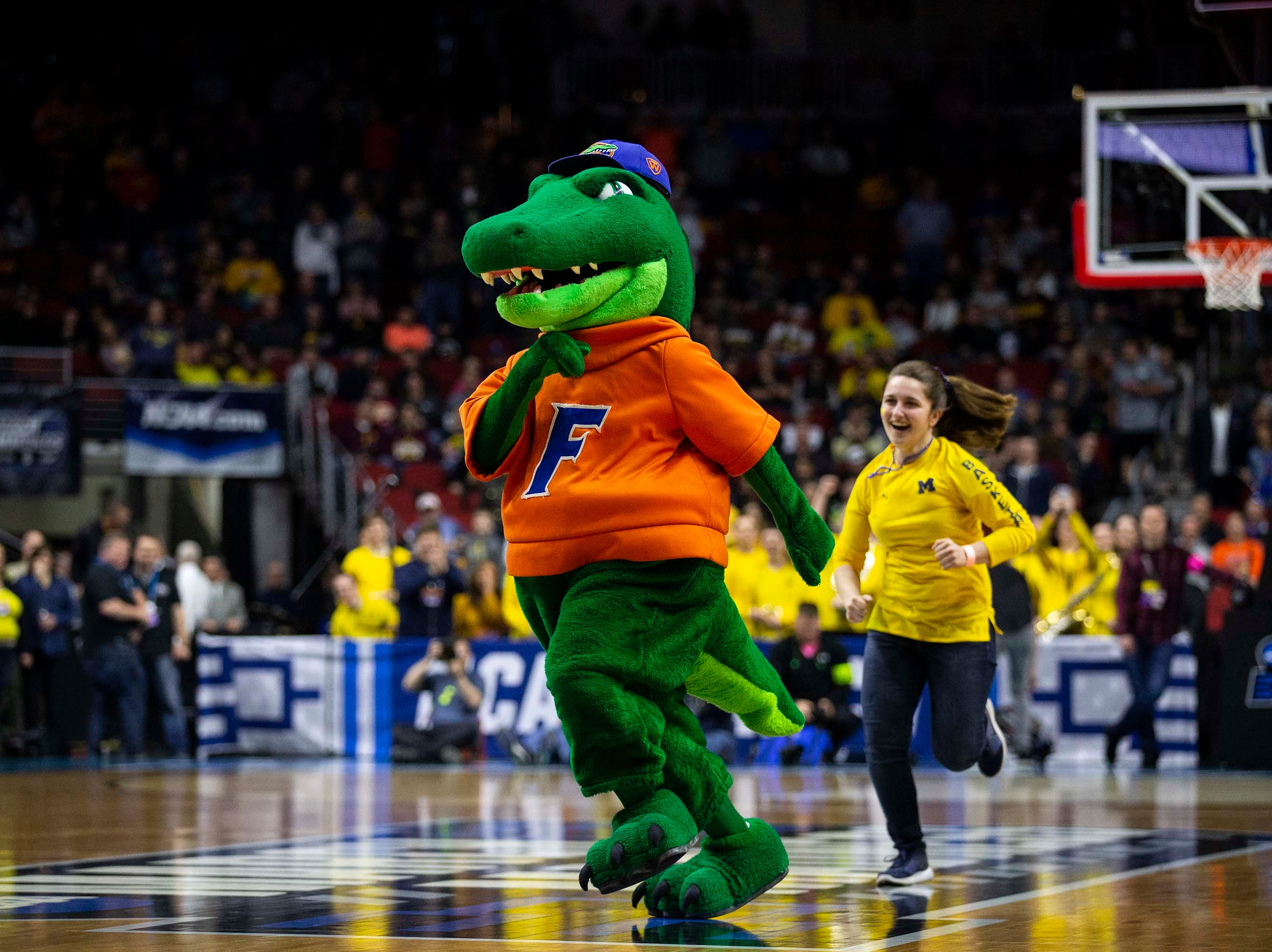 The Florida Gator's mascot runs from a member of the Michigan pep band before the NCAA Tournament second-round match-up between Michigan and Florida on Saturday, March 23, 2019, in Wells Fargo Arena in Des Moines, Iowa.
