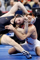 Iowa's Spencer Lee, left, grapples with Oklahoma State's Nicholas Piccinni during their 125-pound match in the semifinals of the NCAA wrestling championships, Friday, March 22, 2019, in Pittsburgh. Lee won and advances to face Virginia's Jack Mueller in the championship Saturday.