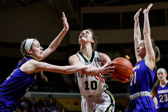 St. Ignace forward Emily Coveyou (10) makes a layup ]against Adrian Lenawee Christian  forward Breanne Salenbien (35) and forward Brooke Brinning (21) during the second half of MHSAA girls Division 4 final at Van Noord Arena in Grand Rapids, Saturday, March 23, 2019.