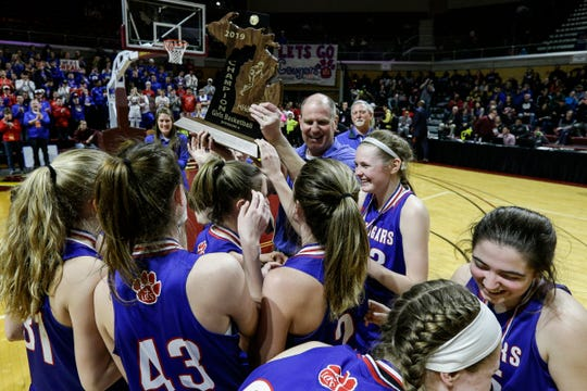 Adrian Lenawee Christian players and head coach Jamie Salenbien celebrate the MHSAA girls Division 4 championship trophy after 48-46 win over St. Ignace at Van Noord Arena in Grand Rapids, Saturday, March 23, 2019.