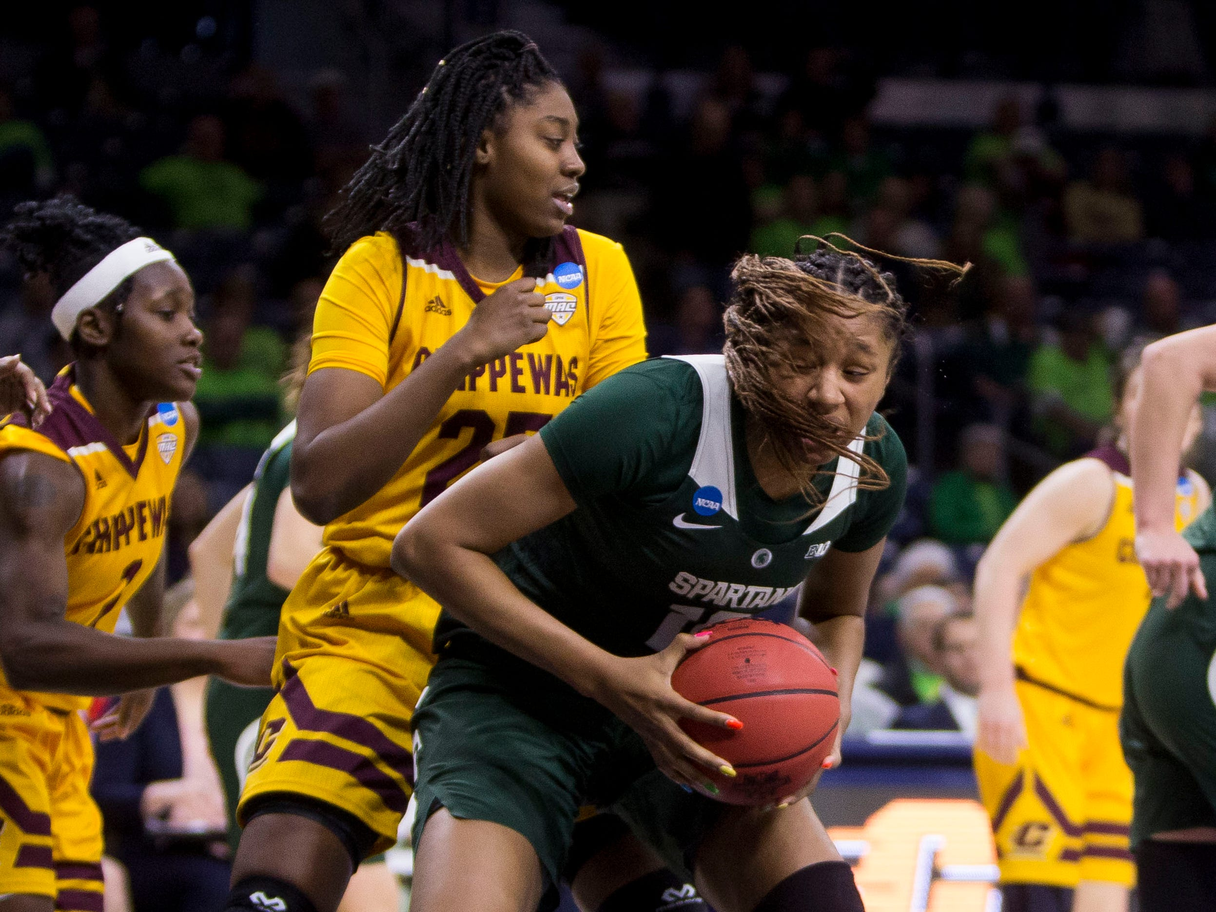Michigan State's Sidney Cooks, front, grabs a rebound in front of Central Michigan's Jahari Smith (25) during a first-round game in the NCAA women's college basketball tournament in South Bend, Ind., Saturday, March 23, 2019. Michigan State won 88-87.