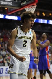 Michigan's Jordan Poole reactions after scoring against Florida during the second half.