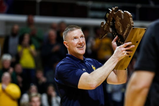 Pewamo-Westphalia head coach Steve Eklund raises the championship trophy after the Pirates won 40-33 over Flint Hamady at the MHSAA girls Division 3 final at Van Noord Arena in Grand Rapids, Saturday, March 23, 2019.