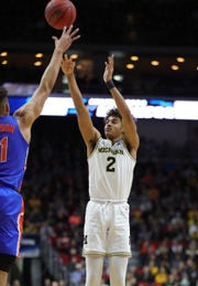 Michigan's Jordan Poole scores against Florida's Keyontae Johnson in the first half of their second round NCAA tournament game Saturday, March 23, 2019 at Wells Fargo Arena in Des Moines, Iowa.