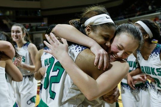 Saginaw Heritage forward Shine Strickland-Gills (32) hugs teammate guard Lauren Gunn (10) after their 55-40 win over Southfield Arts & Technology at the MHSAA girls Division 1 final at Van Noord Arena in Grand Rapids, Saturday, March 23, 2019.