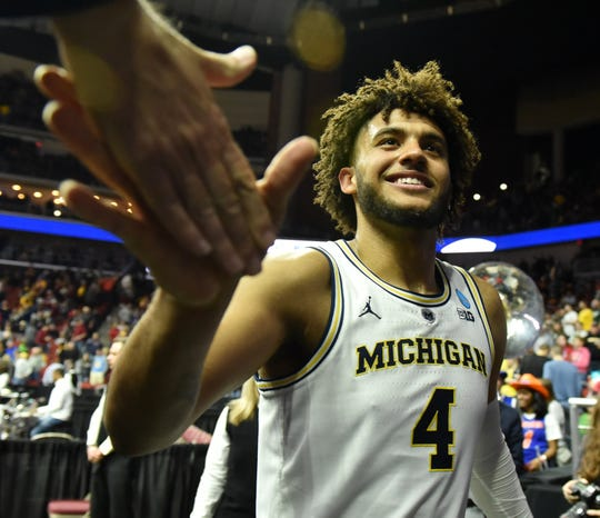 Forward Isaiah Livers (4) celebrates with fans after Michigan defeats Florida, 64-49, Saturday to reach the Sweet 16 for the third consecutive year.