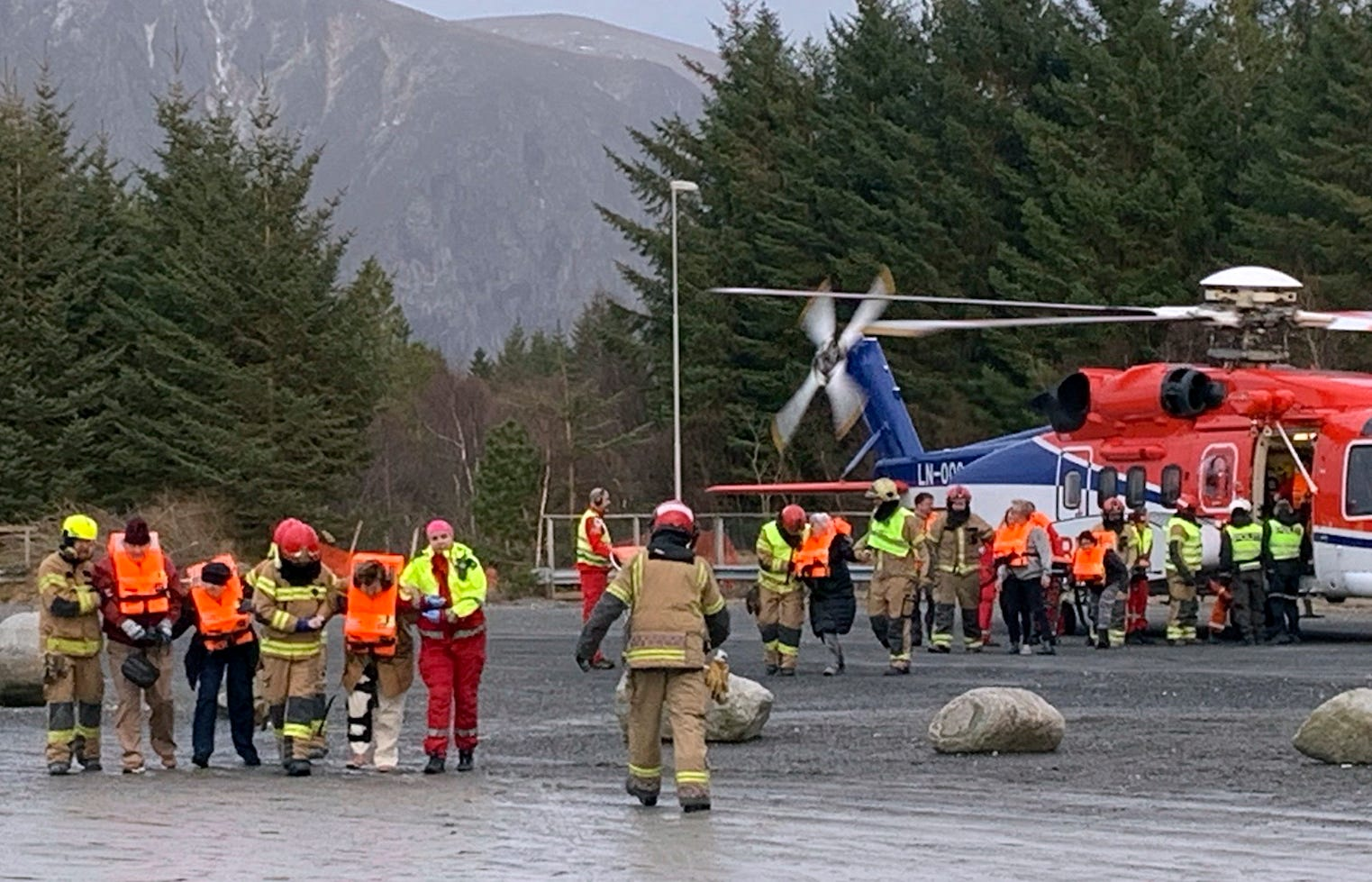 Passengers rescued from the Viking Sky cruise ship are helped from a helicopter in Hustadvika, Norway, Saturday March 23, 2019.