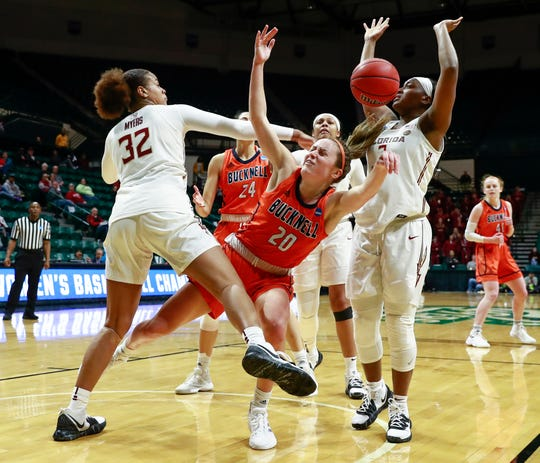 Bucknell guard Kate Walker (20) is tripped up under the basket by Florida State defenders Valencia Myers (32) and Sayawni Lassiter, during the second half a first-round game in the NCAA women's college basketball tournament in Charlotte, N.C.