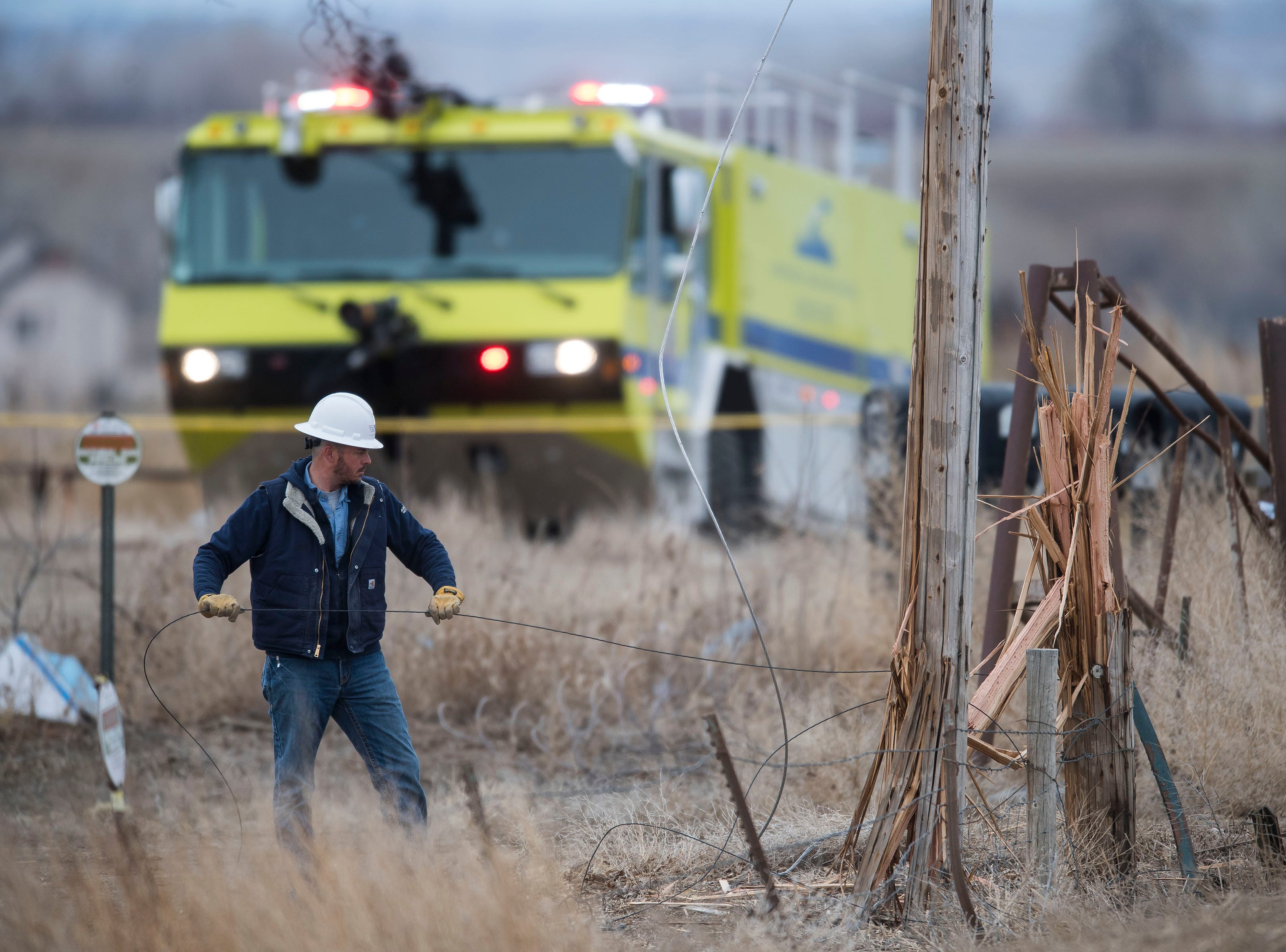 A man works to free a utility pole that was cut in half when a small plane crashed into it, injuring three people onboard, on Saturday, March 23, 2019, west of the Northern Colorado Regional Airport.