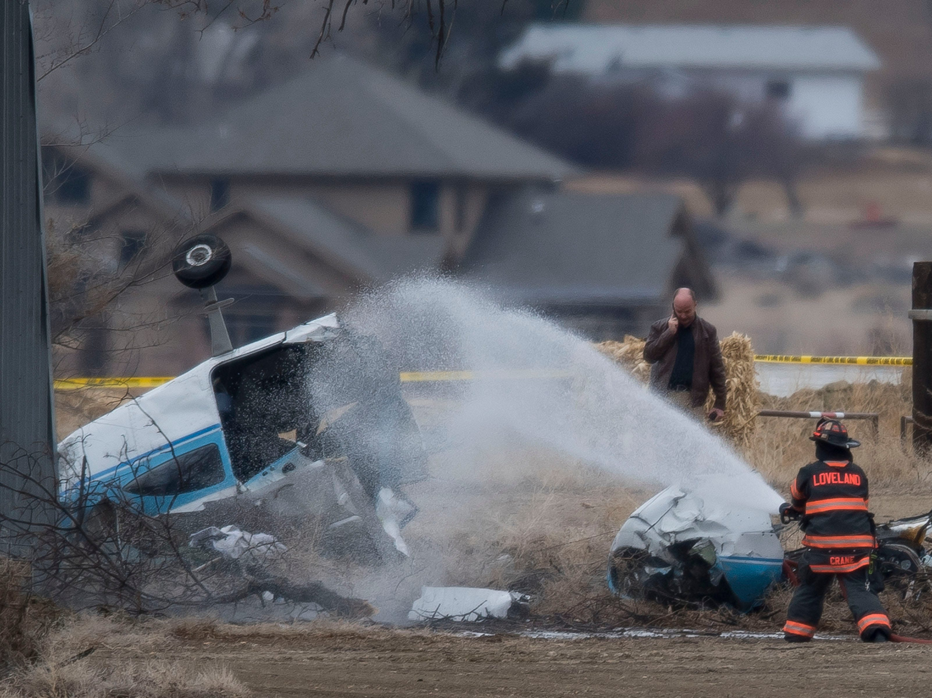 A Loveland firefighter sprays down the fuselage of a small plane that crashed near a dairy farm Saturday, March 23, 2019, injuring three people on board. The crash happened west of the intersection of East County Road 30 and Boyd Lake Avenue in Fort Collins, Colo., just west of the Northern Colorado Regional Airport.