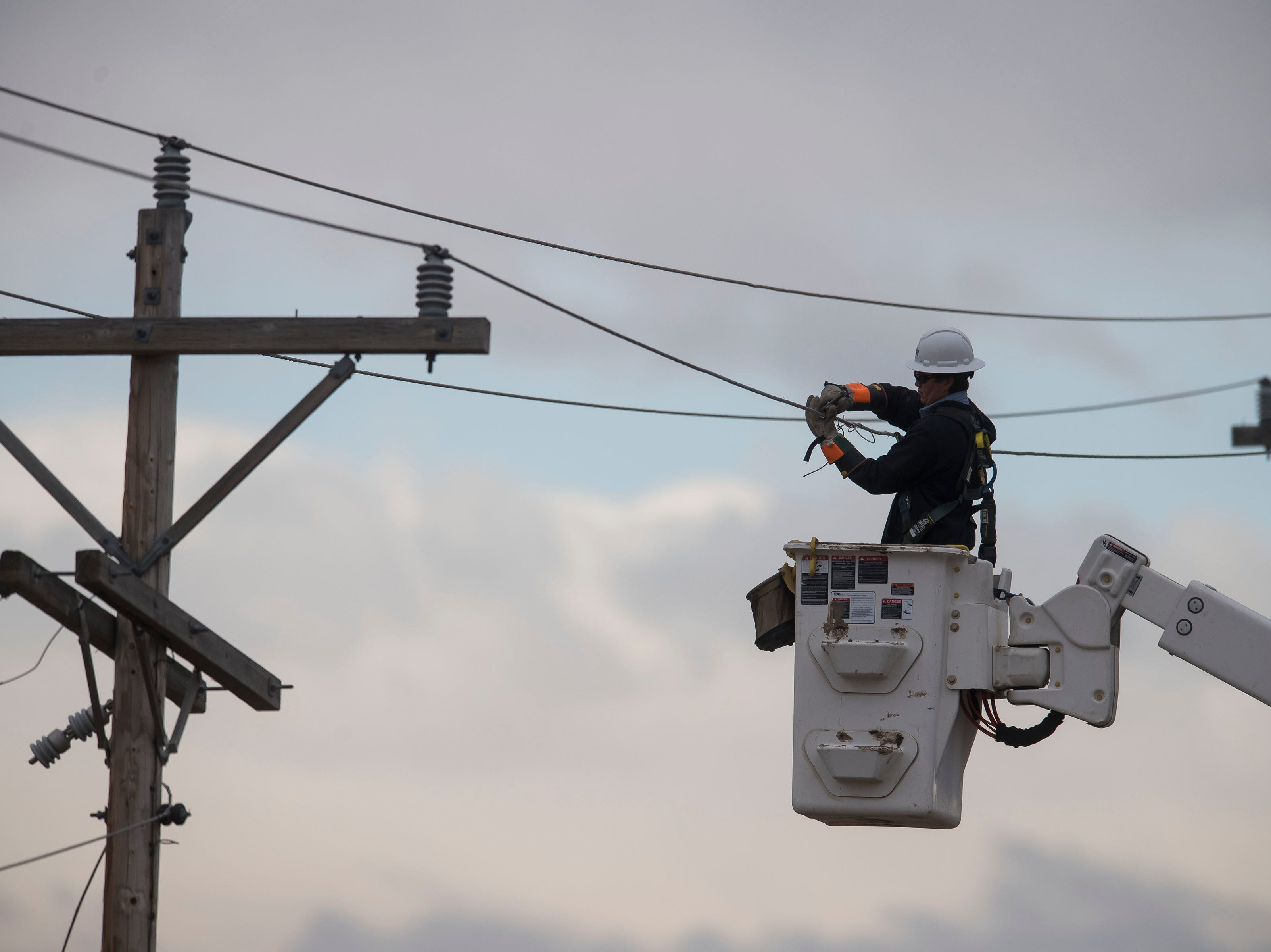 A lineman repairs power lines after a single-engine plane crashed Saturday, March 23, 2019, west of the intersection of East County Road 30 and Boyd Lake Avenue in Fort Collins, Colo. Three people were injured.