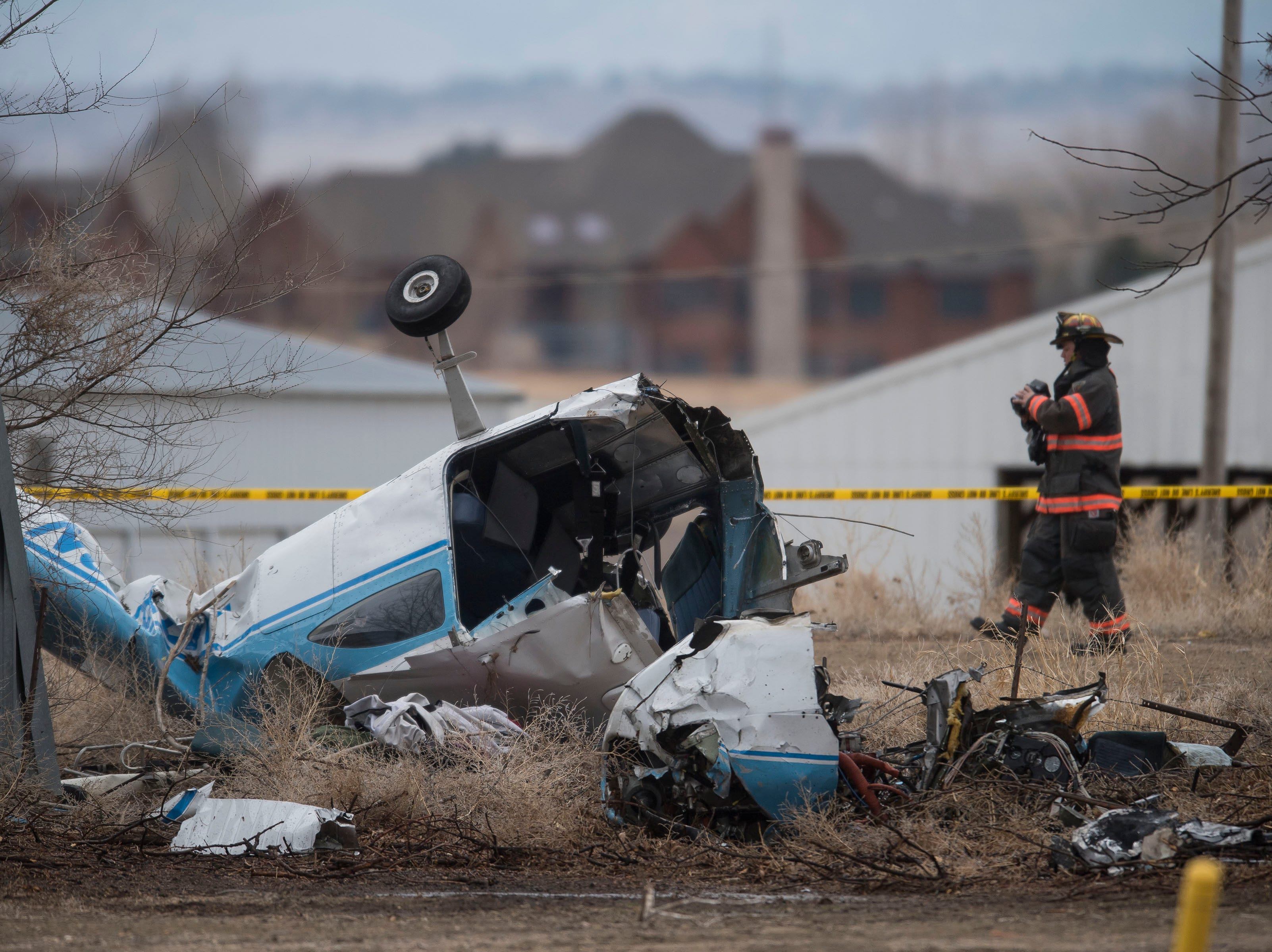 A Loveland firefighter carries a video camera behind the fuselage of a small plane that crashed near the driveway of a dairy farm, injuring three people onboard, on Saturday, March 23, 2019. The plane came to rest west of the intersection of East County Road 30 and Boyd Lake Avenue in Fort Collins, Colo. The crash occurred just west of Northern Colorado Regional Airport.