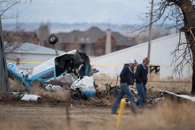 Two men walk past the fuselage of a  single-engine plane that crashed near the driveway of a dairy farm, injuring three people on board, on Saturday, March 23, 2019, west of the intersection of East County Road 30 and Boyd Lake Avenue in Fort Collins, Colo. The crash occurred just west of the Northern Colorado Regional Airport.
