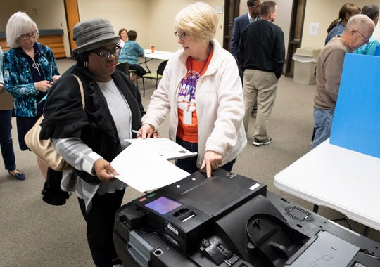 Jennifer Williams (right) shows State Rep. Chandra Dillard how to submit a demo voting ballot at in the Greenville County Elections Office Saturday, March 23, 2019.