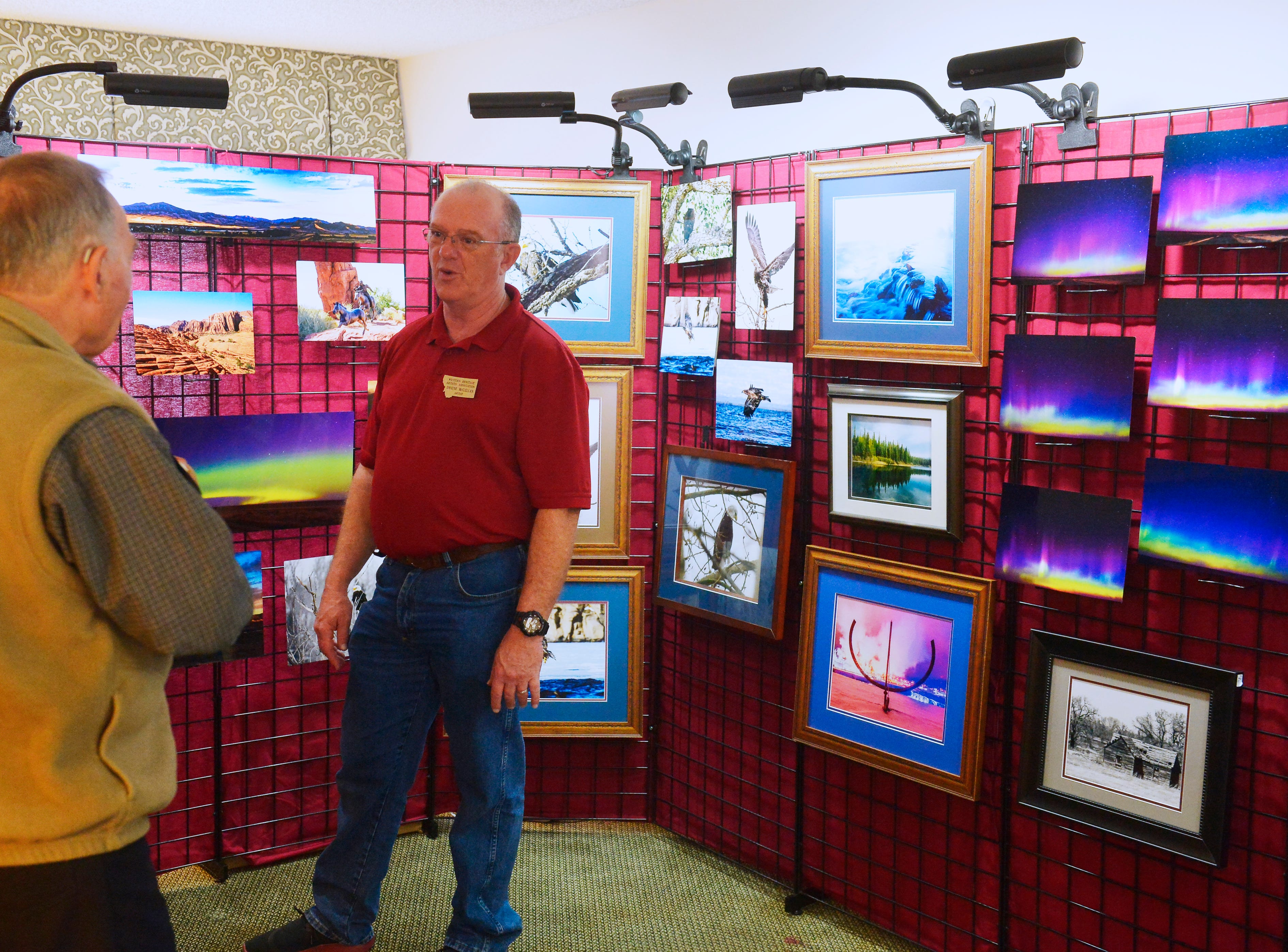 Photographer Dwayne McClellan talks with a guest during the Western Heritage Artists Footprints on the Trail Art Show in the Holiday Inn, Friday.
