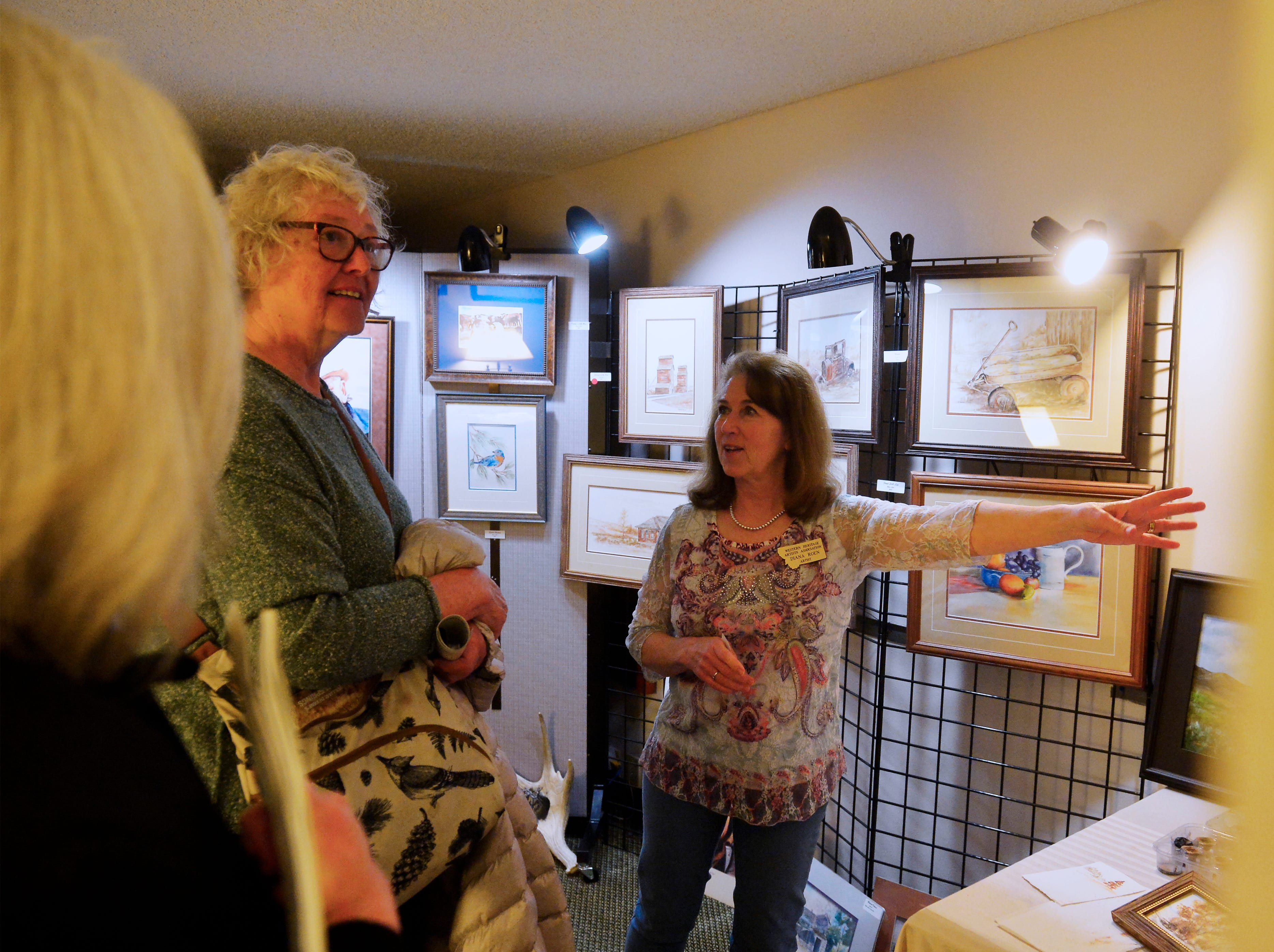 "Diana Roen, right, talks about painting with soil, which she calls ""earth art"", at the Western Heritage Artists Footprints on the Trail Art Show in the Holiday Inn, Friday."