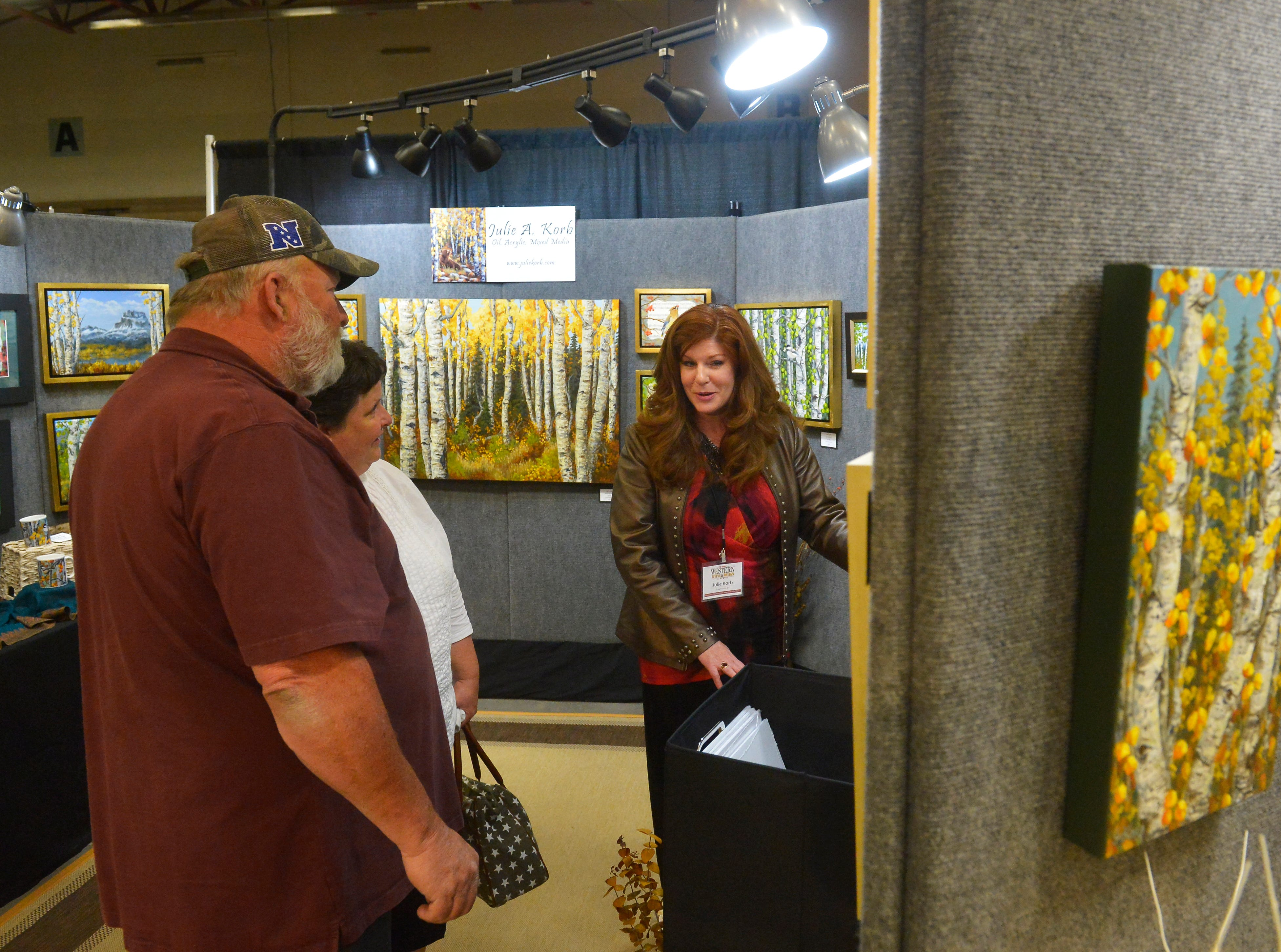 Julia Korb talks with guests to her booth at the Great Western Living and Design Show in the Four Seasons Arena on Friday.